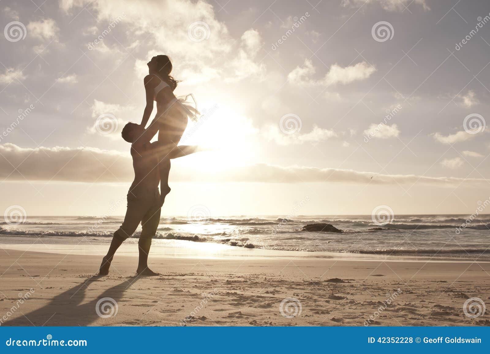 Silhouet die van romantisch paar op strand dansen