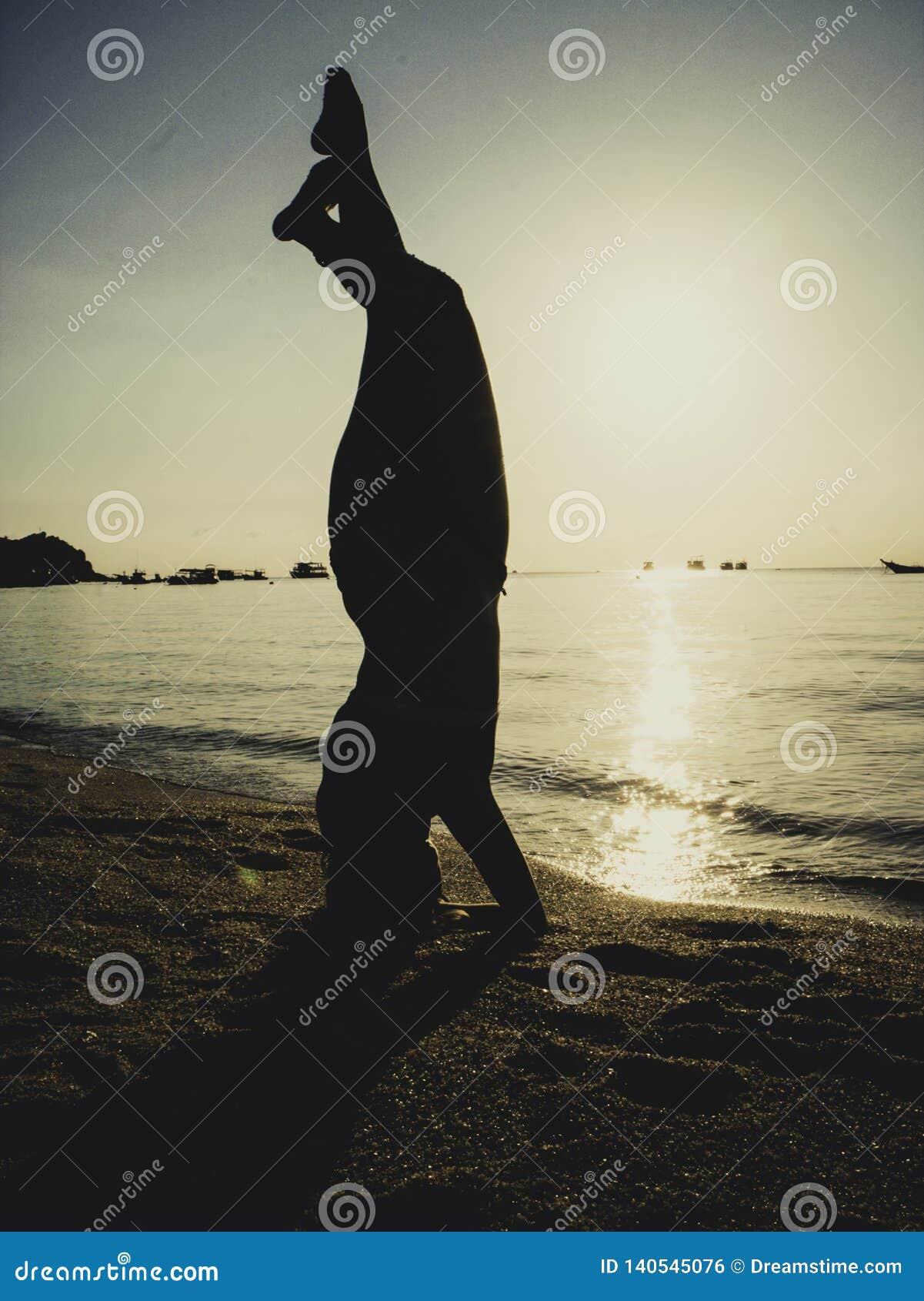 Silhouet jonge vrouw het praktizeren yoga op het strand bij zonsondergang