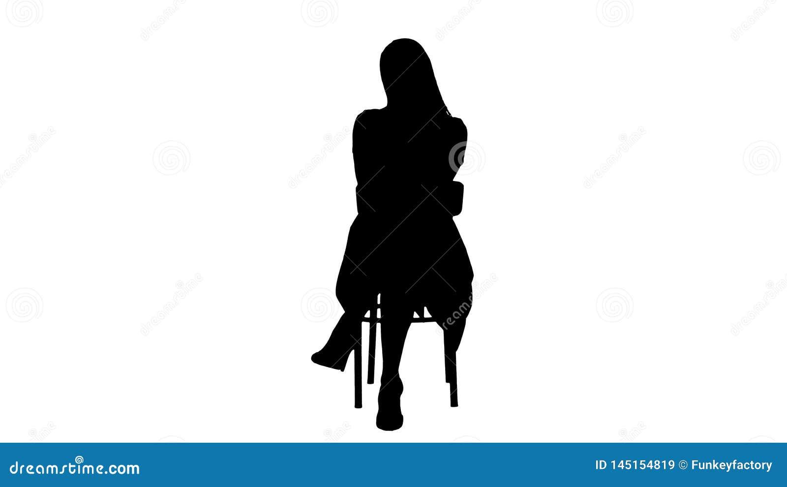 Silhouet Mooie jonge vrouw, meisje, modelblonde met lange haarzitting op een stoel en het kijken aan camera