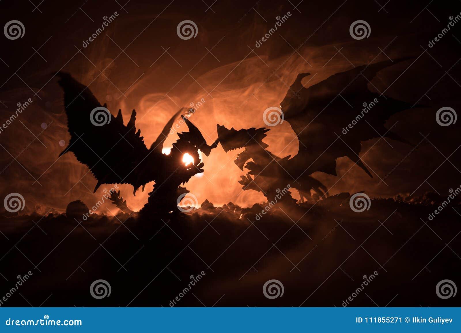 Silhouet van brand ademhalingsdraak met grote vleugels op een donkeroranje achtergrond