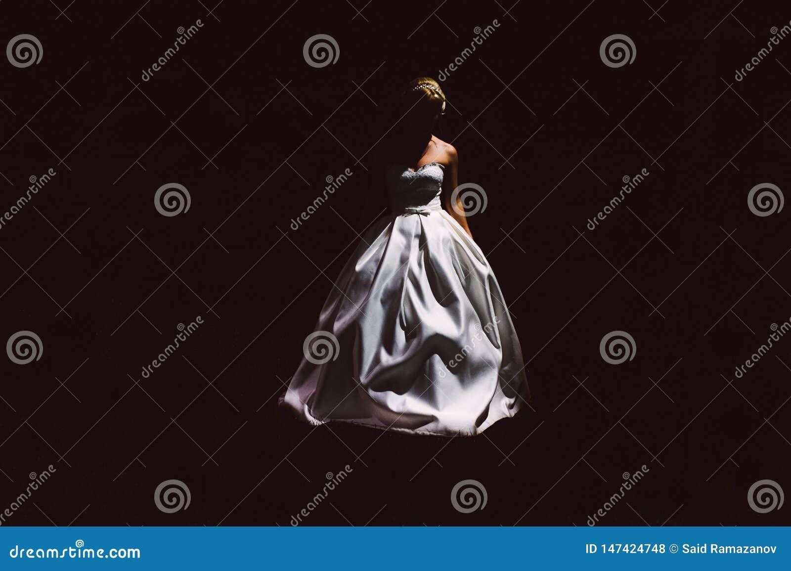 Silhouet van bruid in een witte kleding op zwarte achtergrond