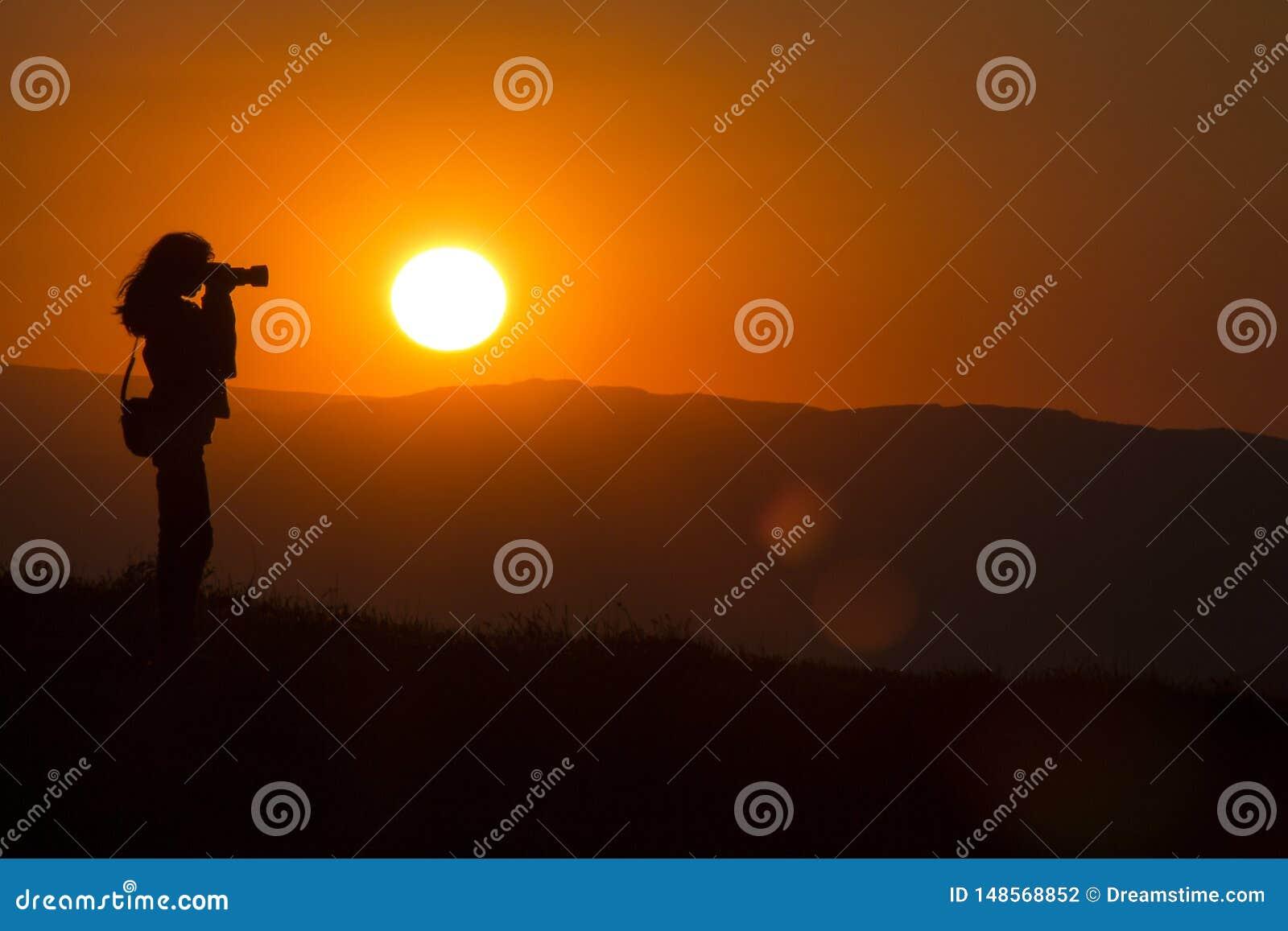 Silhouet van de fotograaf bij zonsondergang