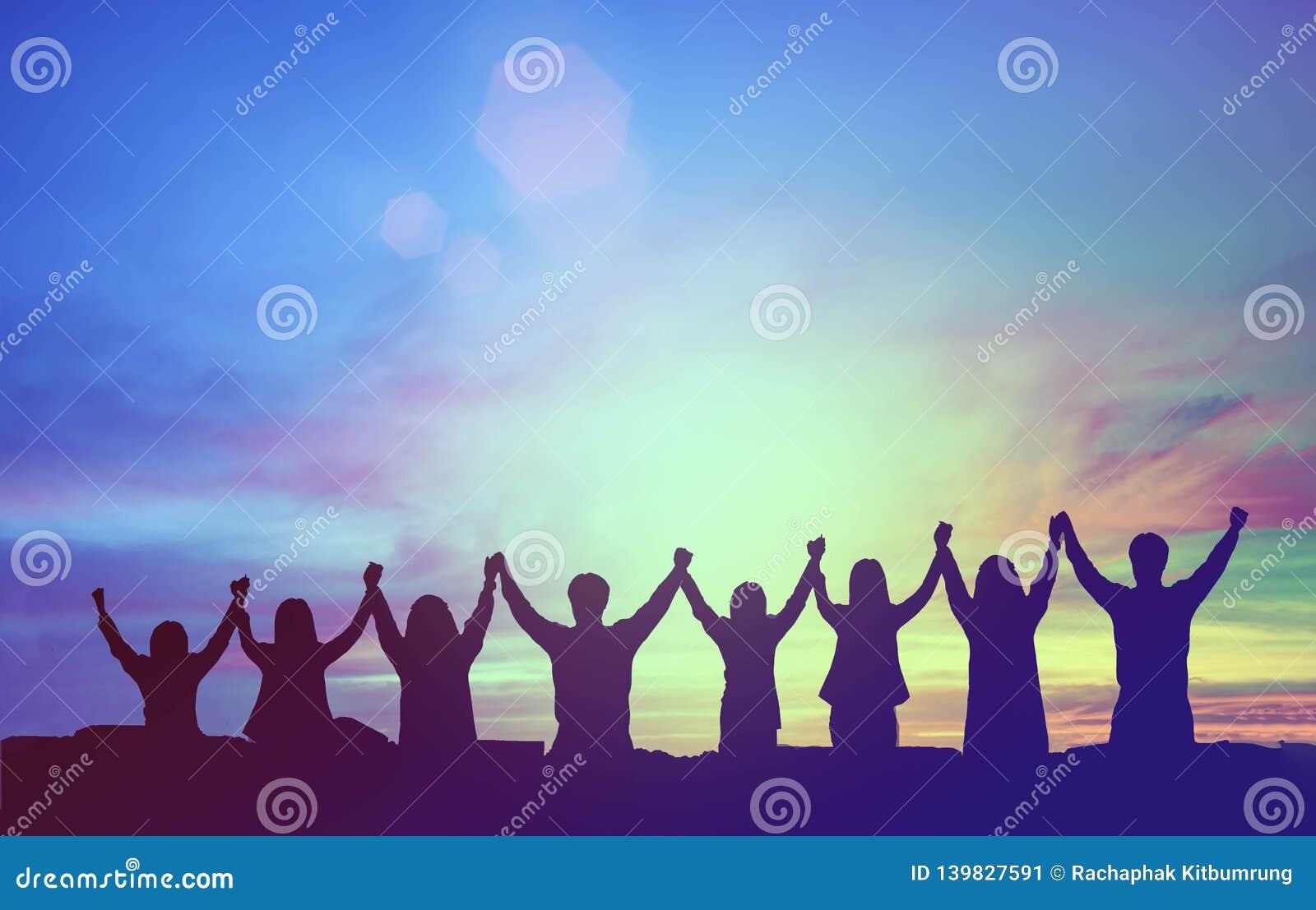 Silhouet van de gelukkige handen van de groepswerkgreep omhoog als succesvolle zaken, overwinning Bedrijfsdoelvoltooiing, geraakt