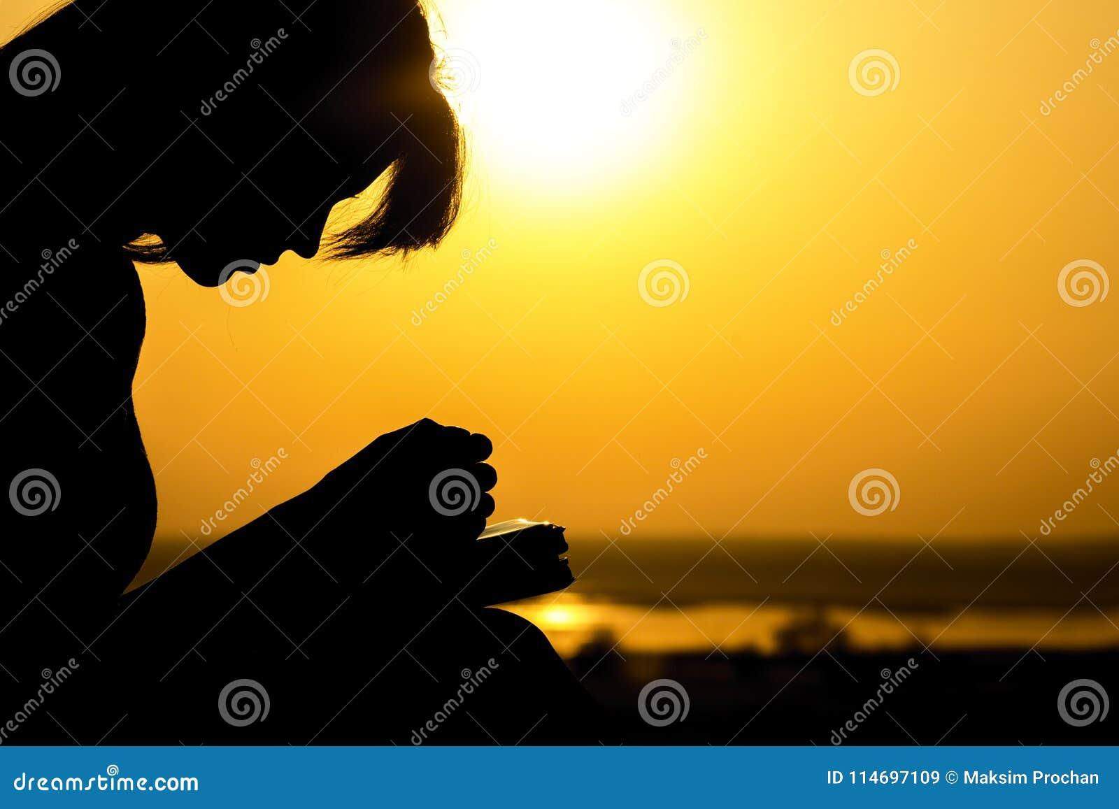 Silhouet van de handen van vrouw die aan God in de aard witth de Bijbel bidden bij zonsondergang, het concept godsdienst en spiri