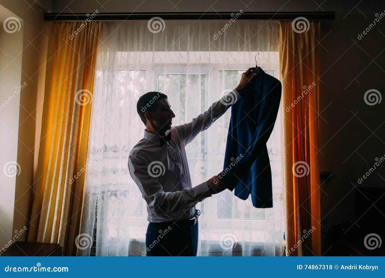 Silhouet van de jonge elegante luxueuze mens die zijn jasje in hotelruimte houden met venster op een achtergrond