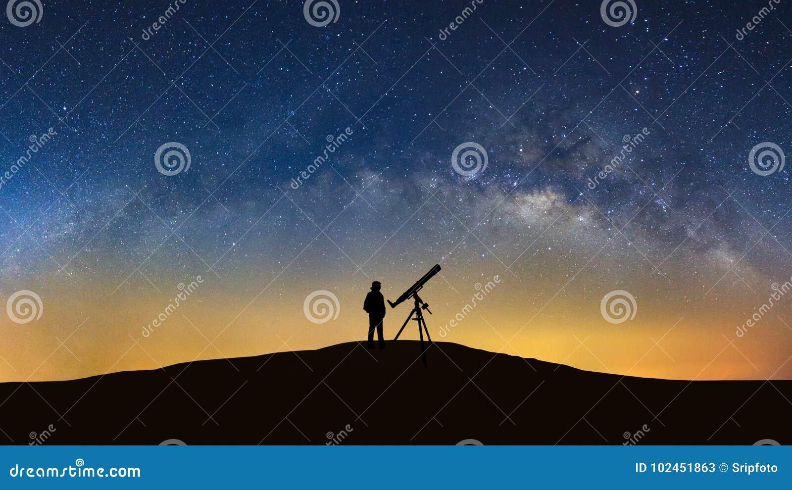 Silhouet van een bevindende mens die met telescoop op wilky w letten