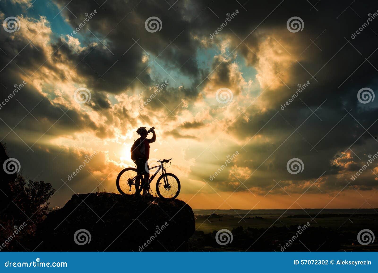 Silhouet van een fietser en een fiets op hemelachtergrond