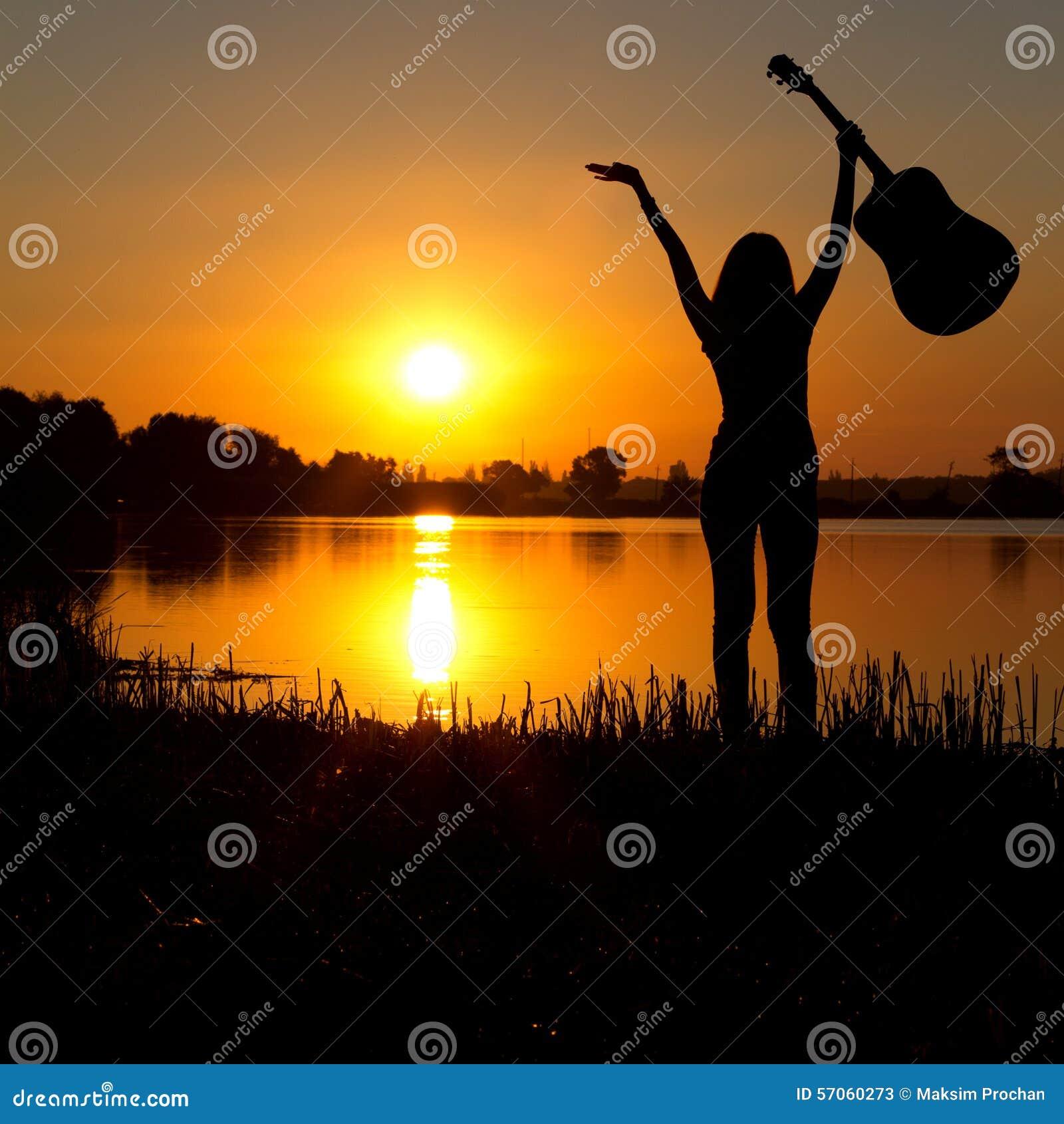Silhouet van een gelukkig meisje met een gitaar op een zonsopgang