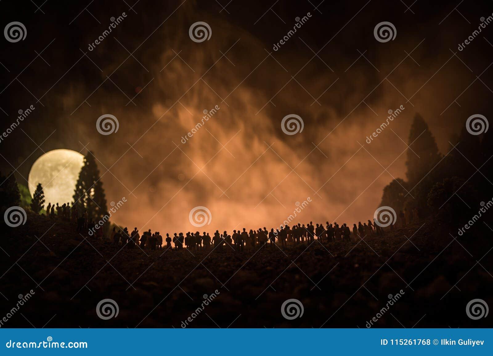 Silhouet van een grote menigte van mensen in bos bij nacht het letten op bij het toenemen grote volle maan Verfraaide achtergrond
