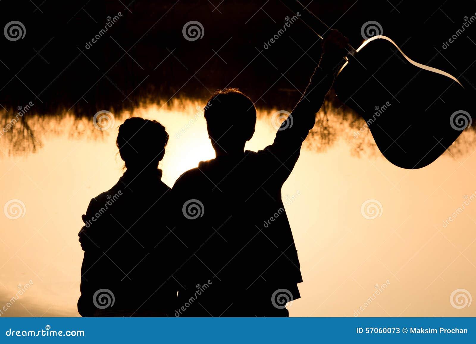 Silhouet van een jong jongen en een meisje op het strand met een gitaar