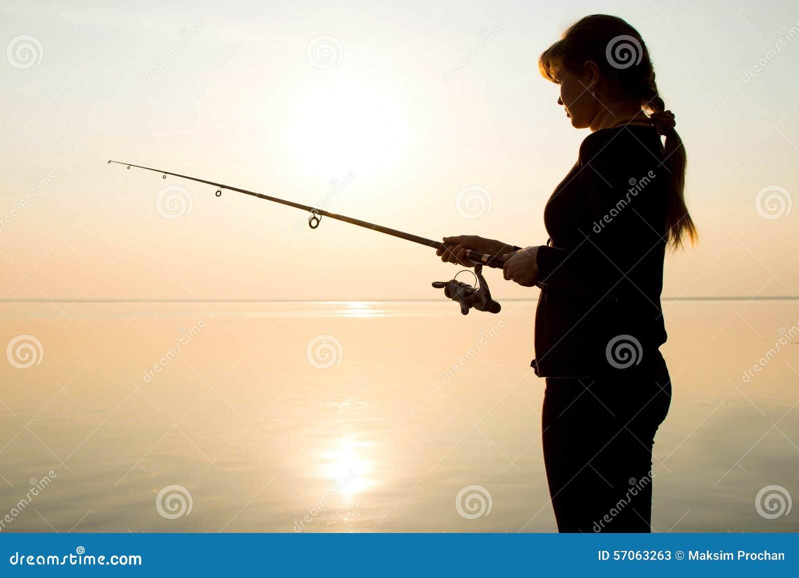 Silhouet van een jong meisje die bij zonsondergang dichtbij vissen