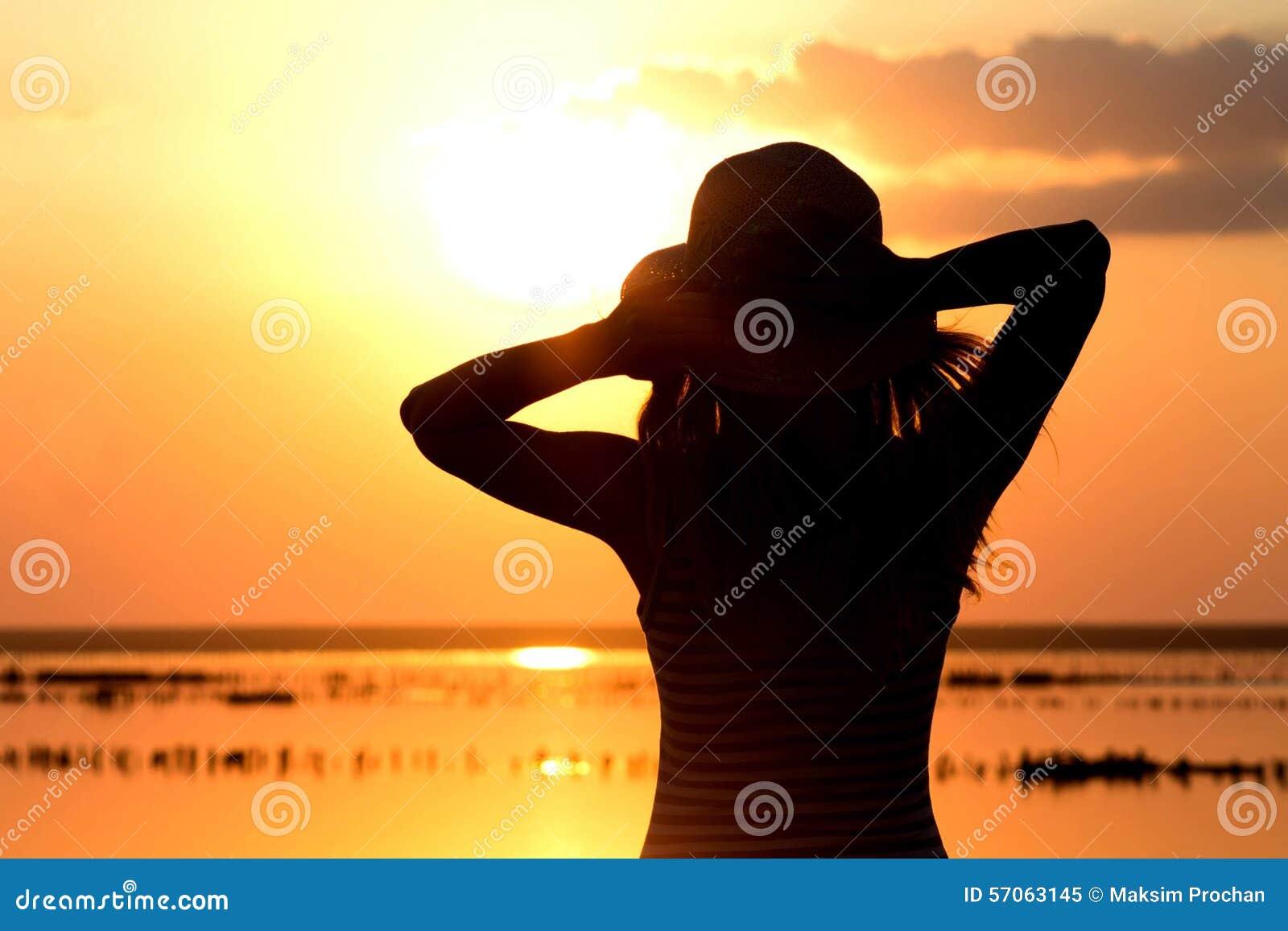 Silhouet van een jong meisje op het overzees in een hoed