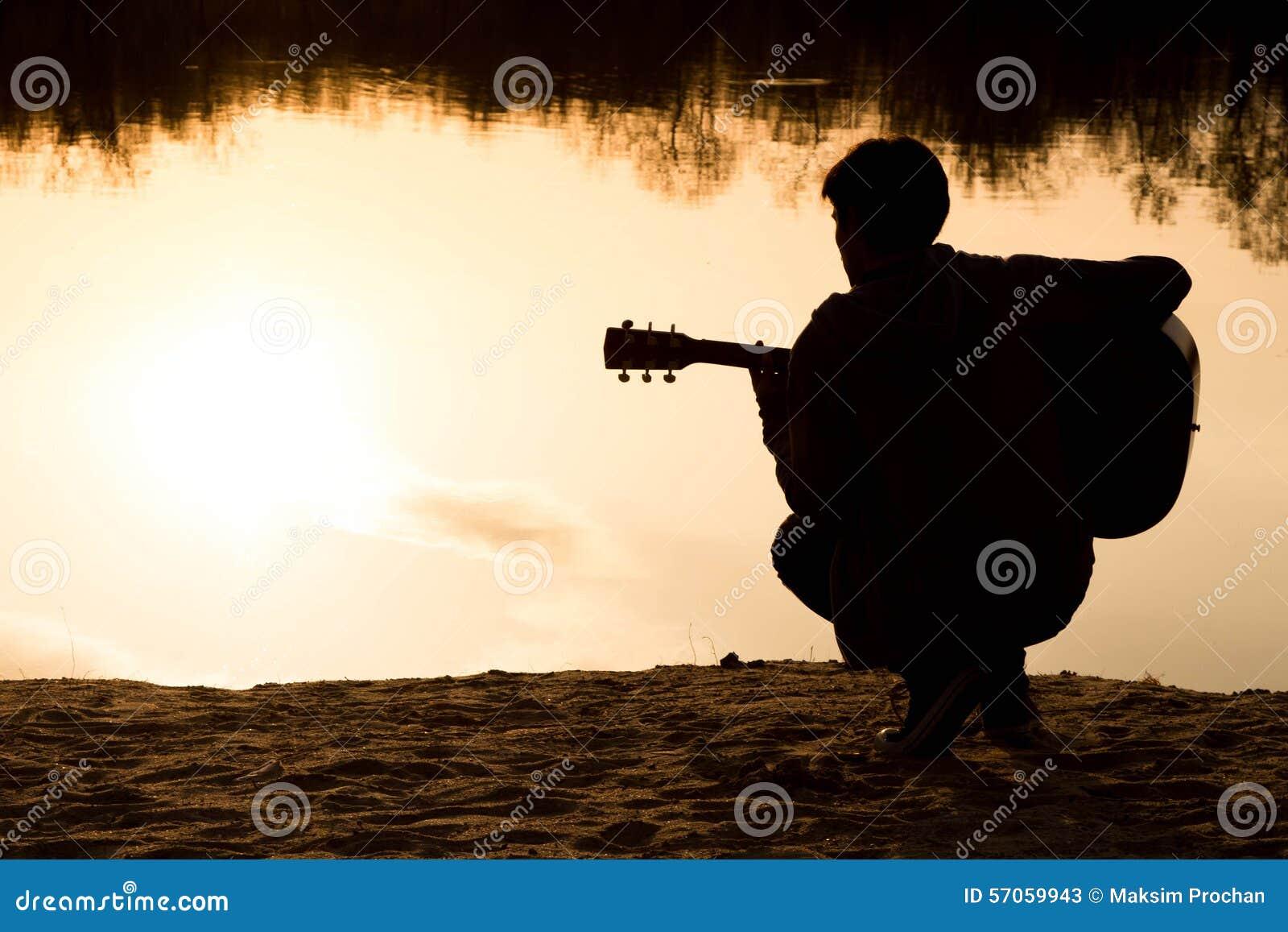Silhouet van een jonge mens met een gitaar