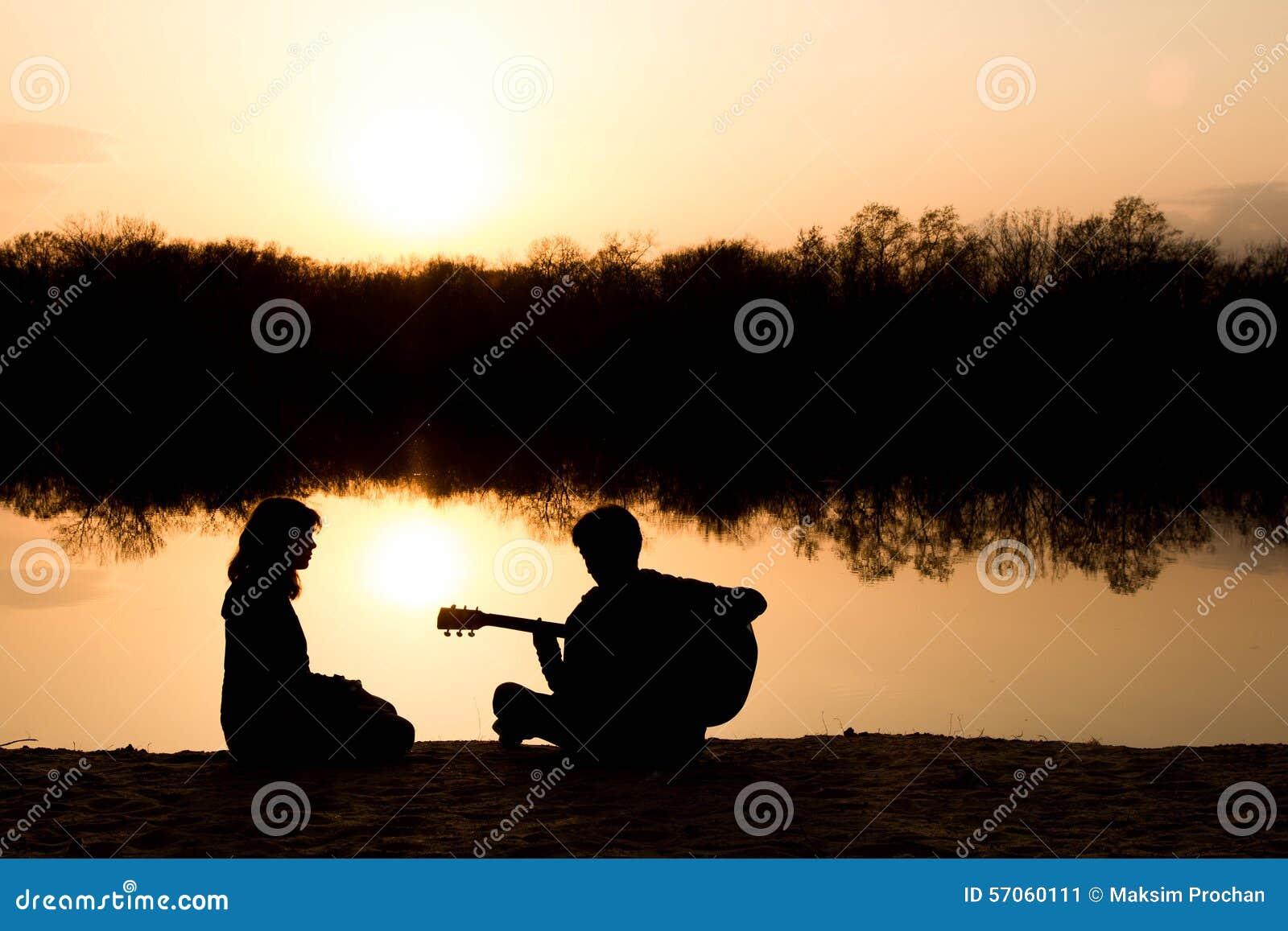 Silhouet van een jongen en een meisje op het strand met een gitaar