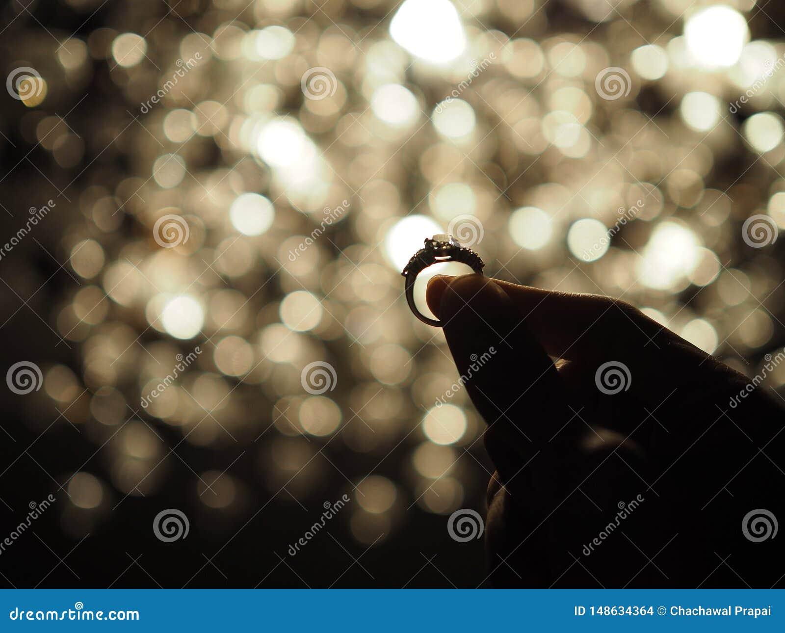 Silhouet van een mannelijke hand die een grote diamantring met gele bokeh lichte achtergrond houden vaas toe