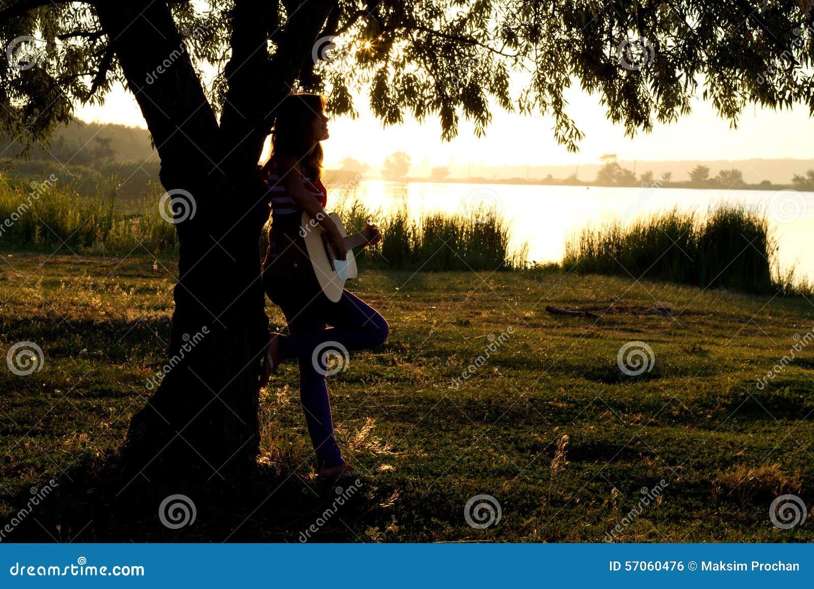 Silhouet van een meisje die een gitaar spelen