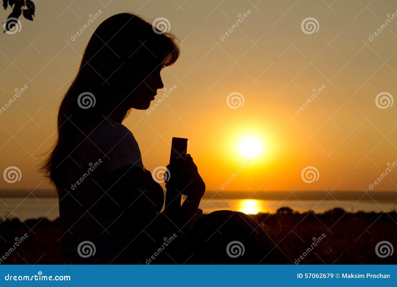 Silhouet van een meisje die met de Bijbel bidden