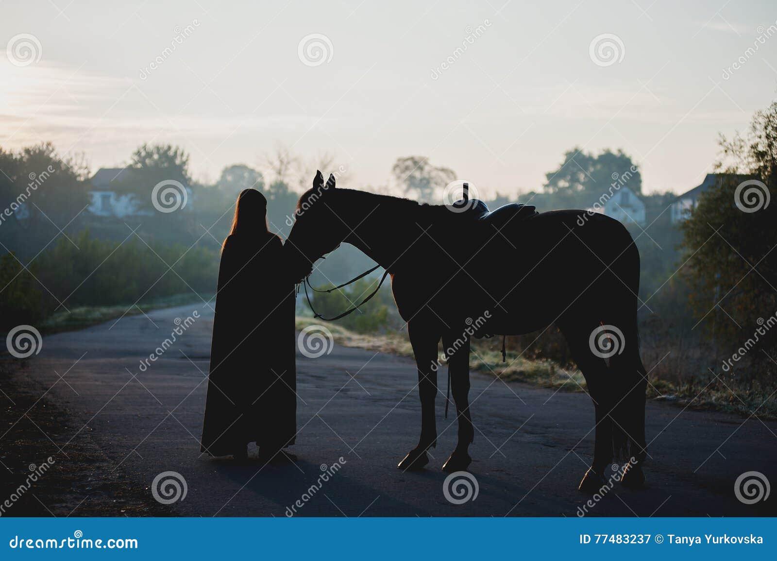 b53a00435bb Silhouet van een meisje in een regenjas die een paard op donkere  achtergrond met blauwe mist