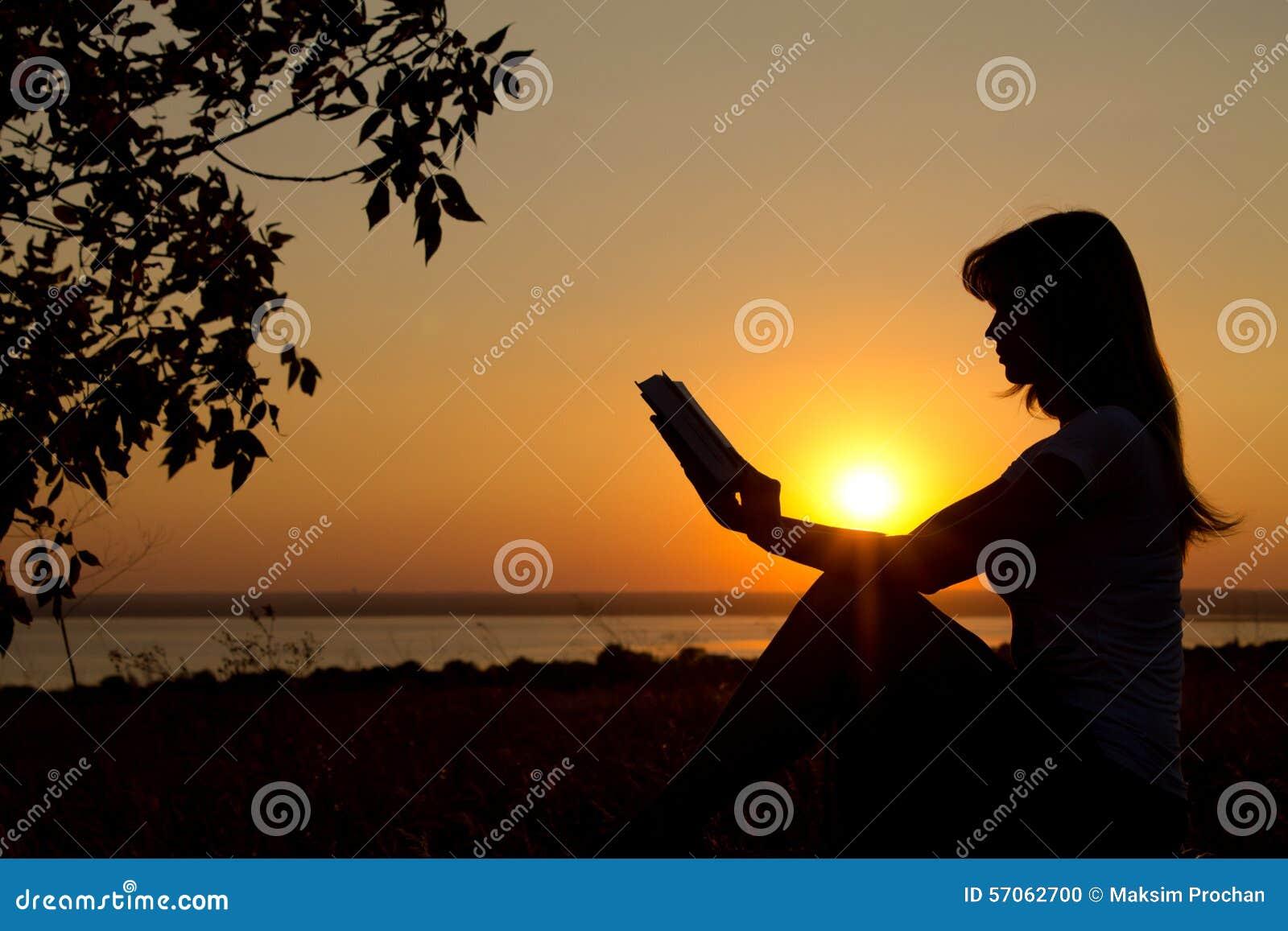 Silhouet van een meisje met een boek in handen bij zonsondergang