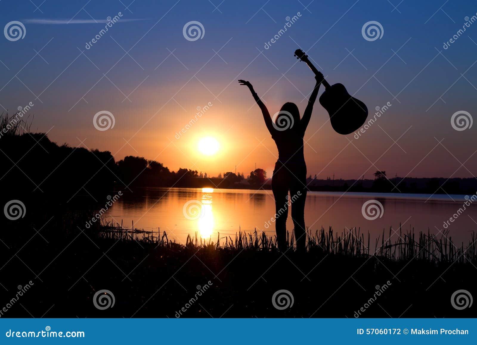 Silhouet van een meisje met een gitaar op de aard