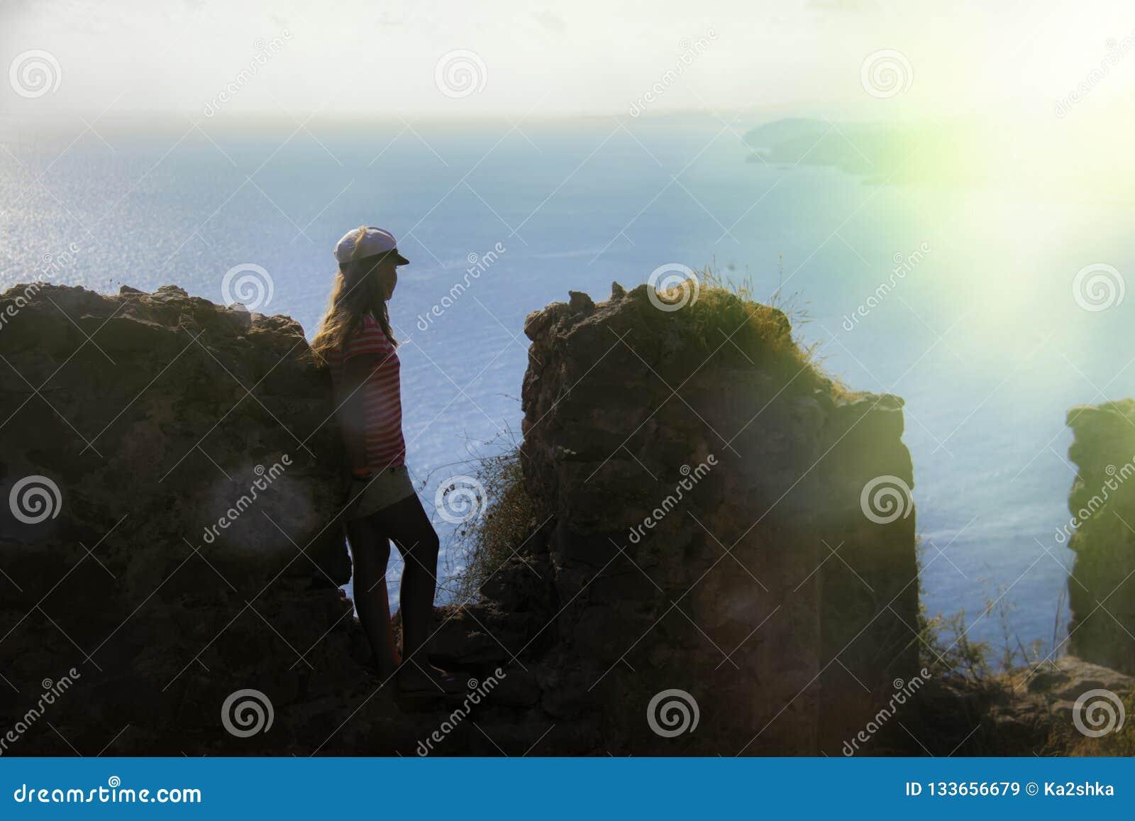 Silhouet van een meisje op de achtergrond van de overzeese achtergrond en steenmuur