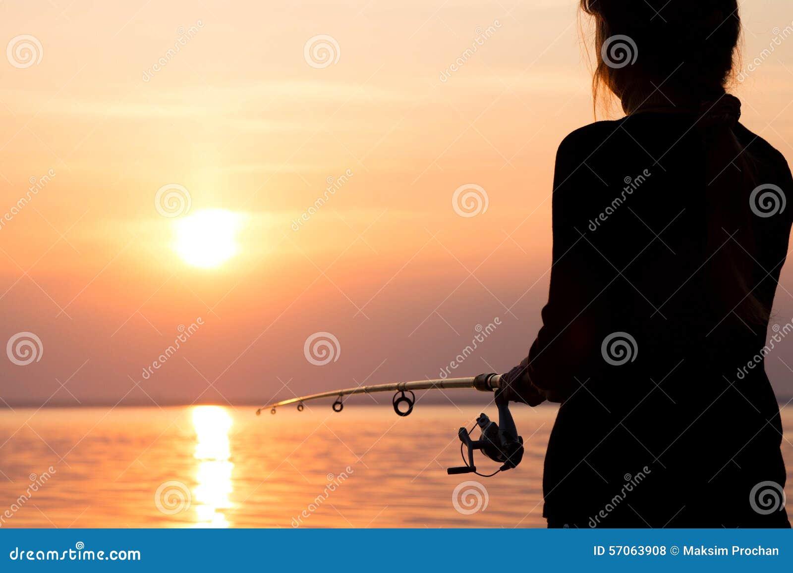Silhouet van een meisje op de bank van de rivier met een hengel