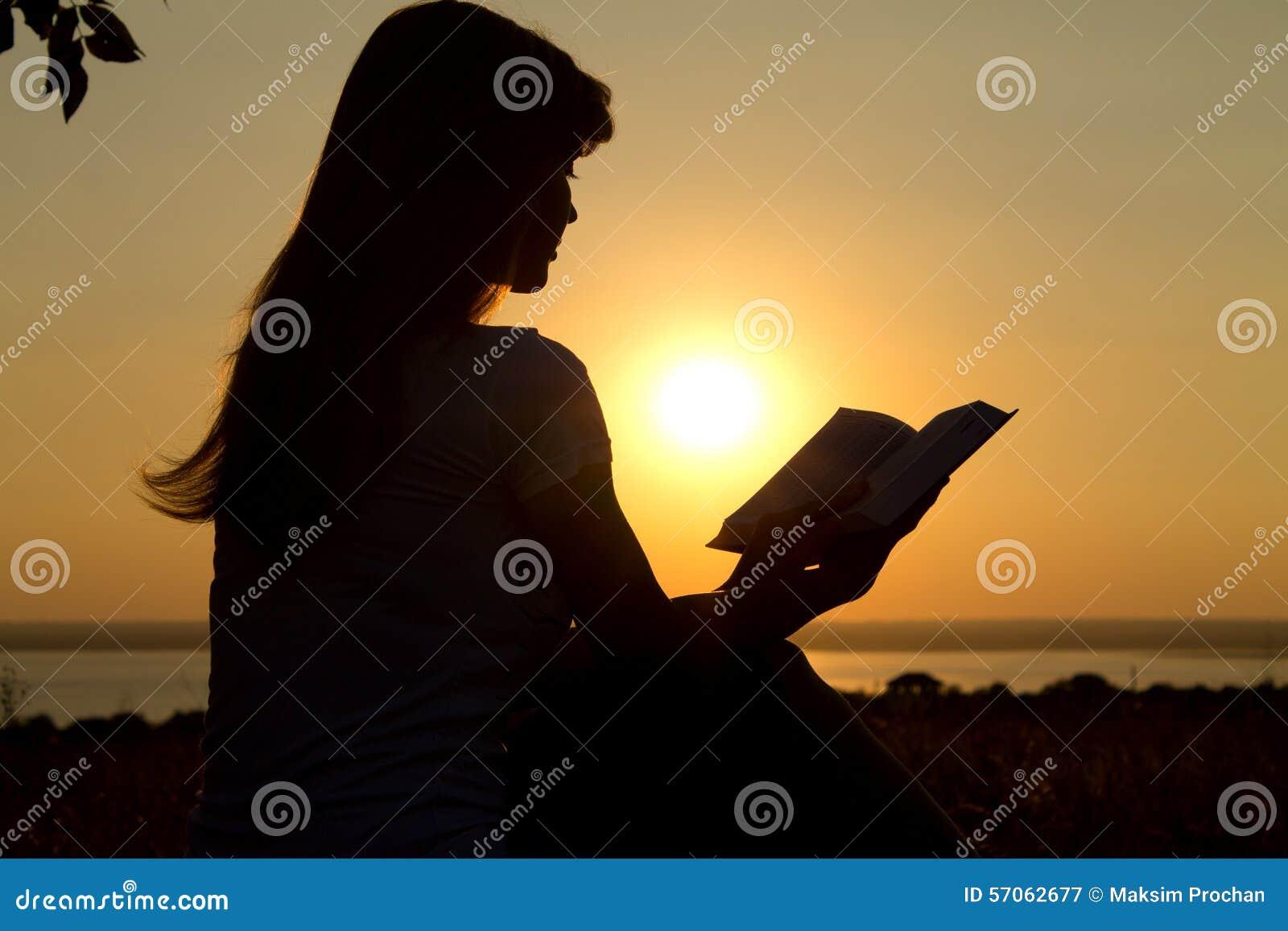 Silhouet van een meisjeslezing bij zonsondergang