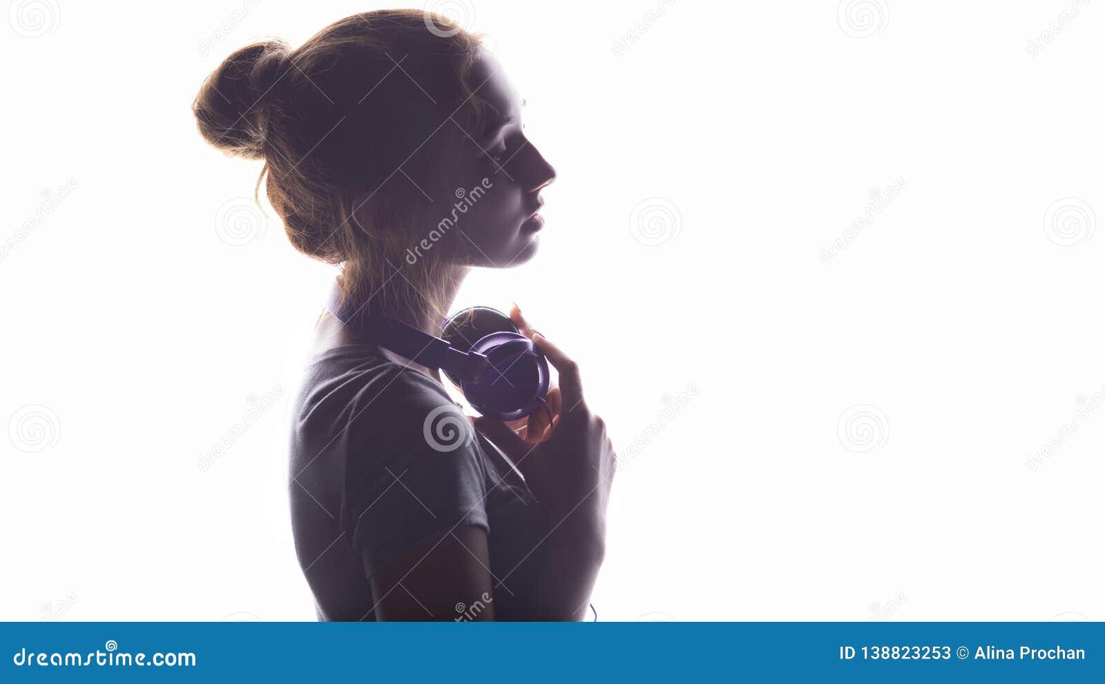 Silhouet van een romantisch meisje die aan muziek in hoofdtelefoons, het jonge vrouw ontspannen op een witte achtergrond luistere