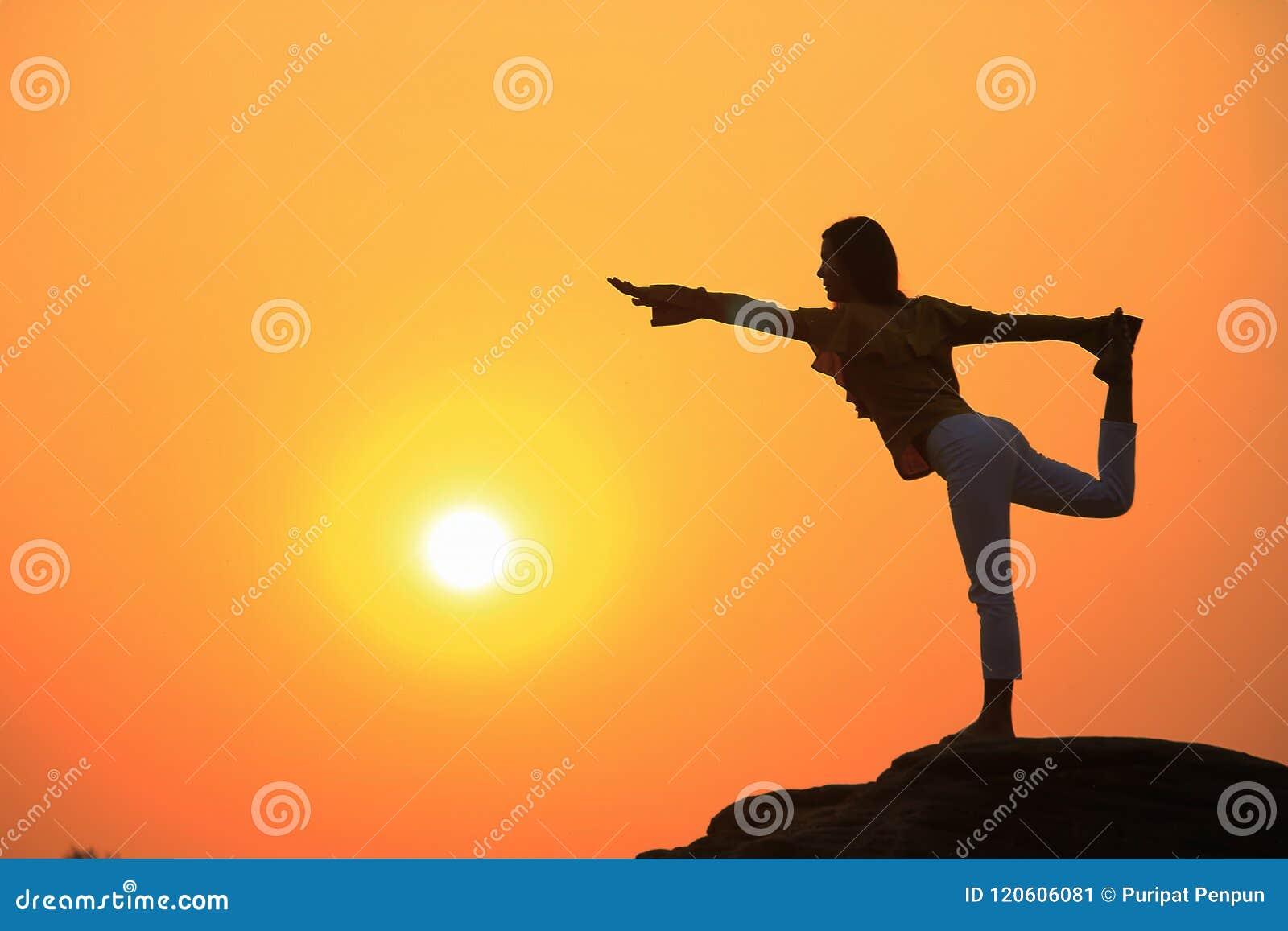 Silhouet van een vrouw het praktizeren yoga op een rots