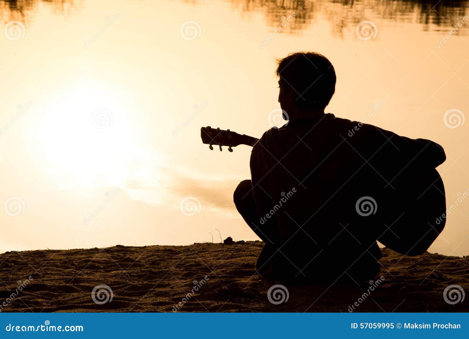Silhouet van een zitting van de jonge mensen speelgitaar op het zand