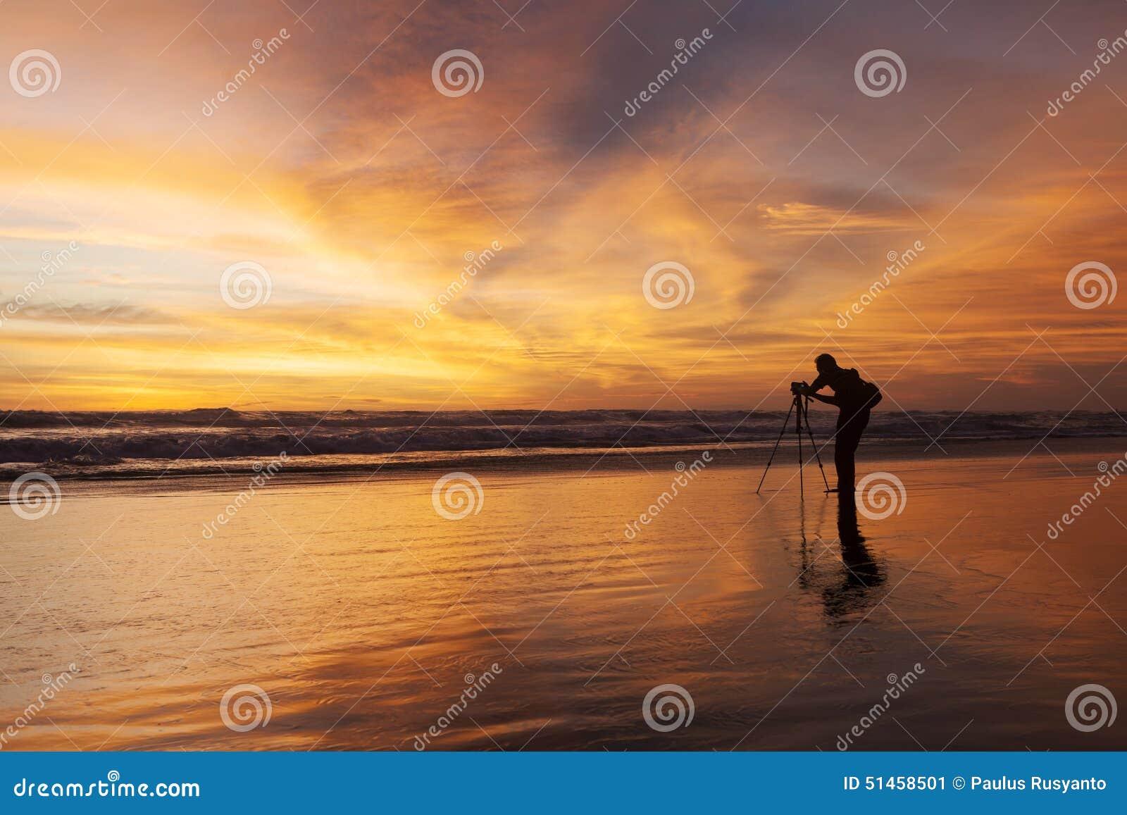 Silhouet van fotograaf op het strand