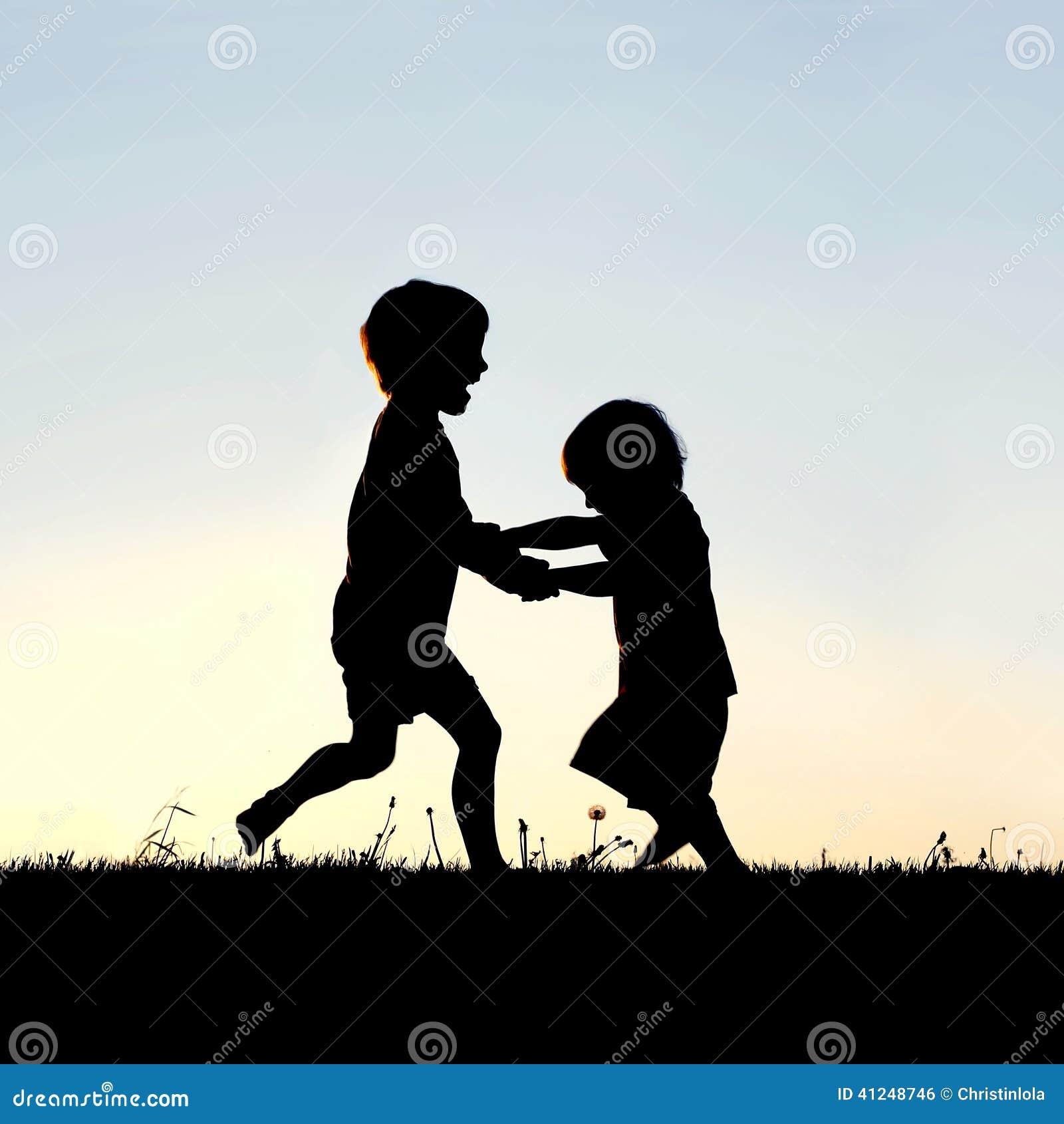 Silhouet van Gelukkige Kleine Kinderen die bij Zonsondergang dansen