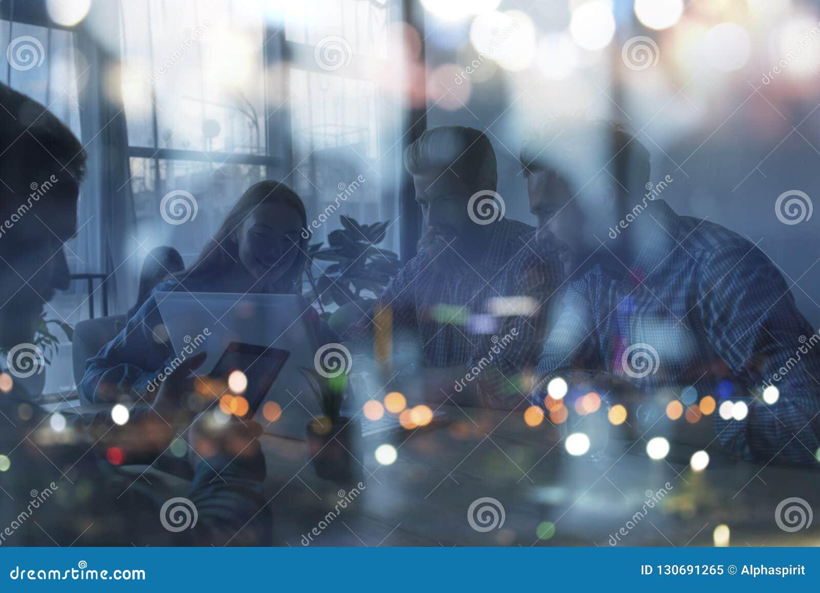 Silhouet van het bedrijfsmensenwerk samen in bureau Concept groepswerk en vennootschap Dubbele blootstelling