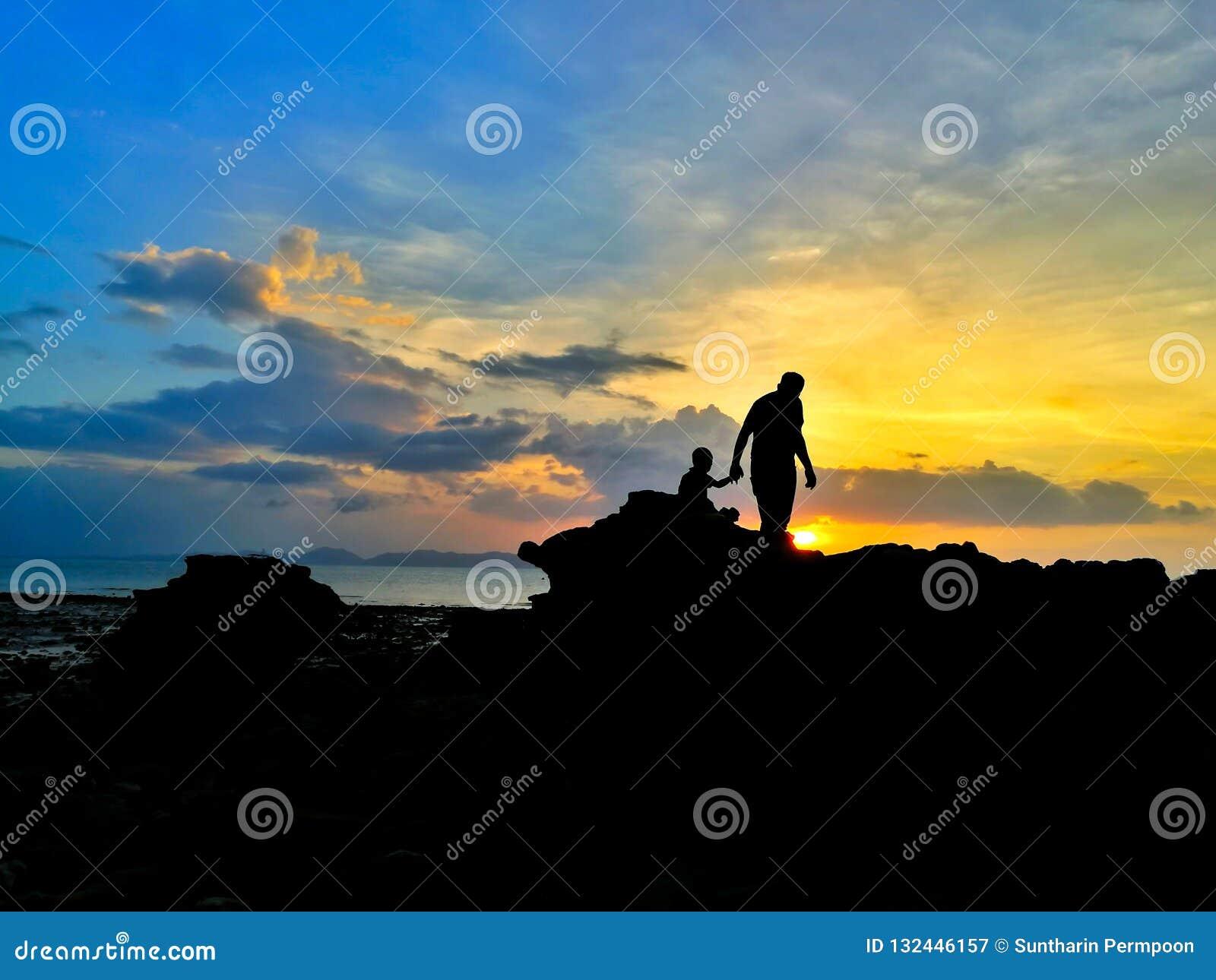 Silhouet van het houden van van vader en zoon op kust en beauti wordt gelopen die