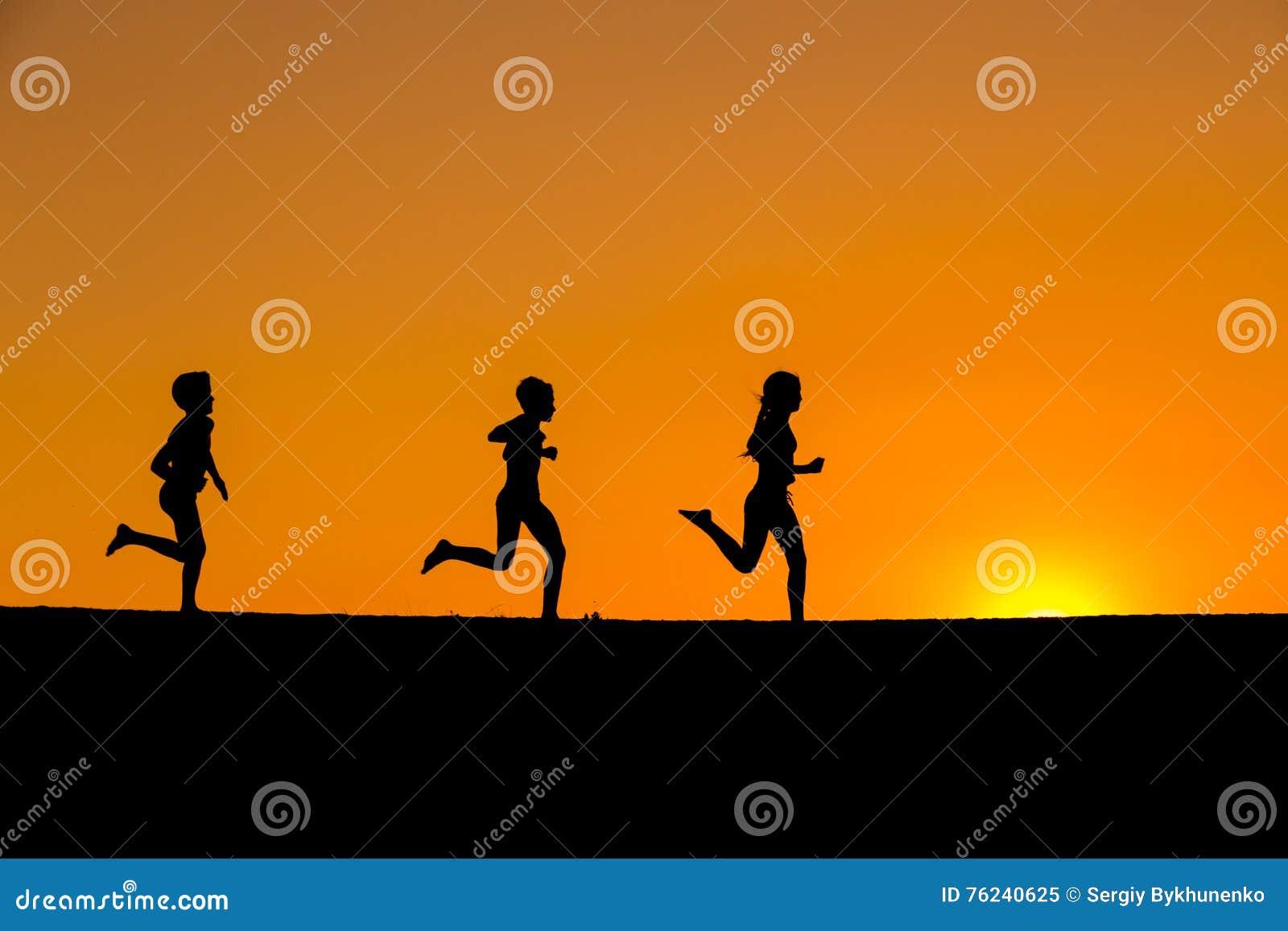 Silhouet van het lopen jonge geitjes tegen zonsondergang
