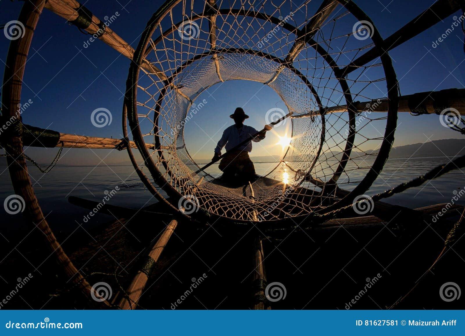 Silhouet van inthavisser tegen de zonsonderganghemel