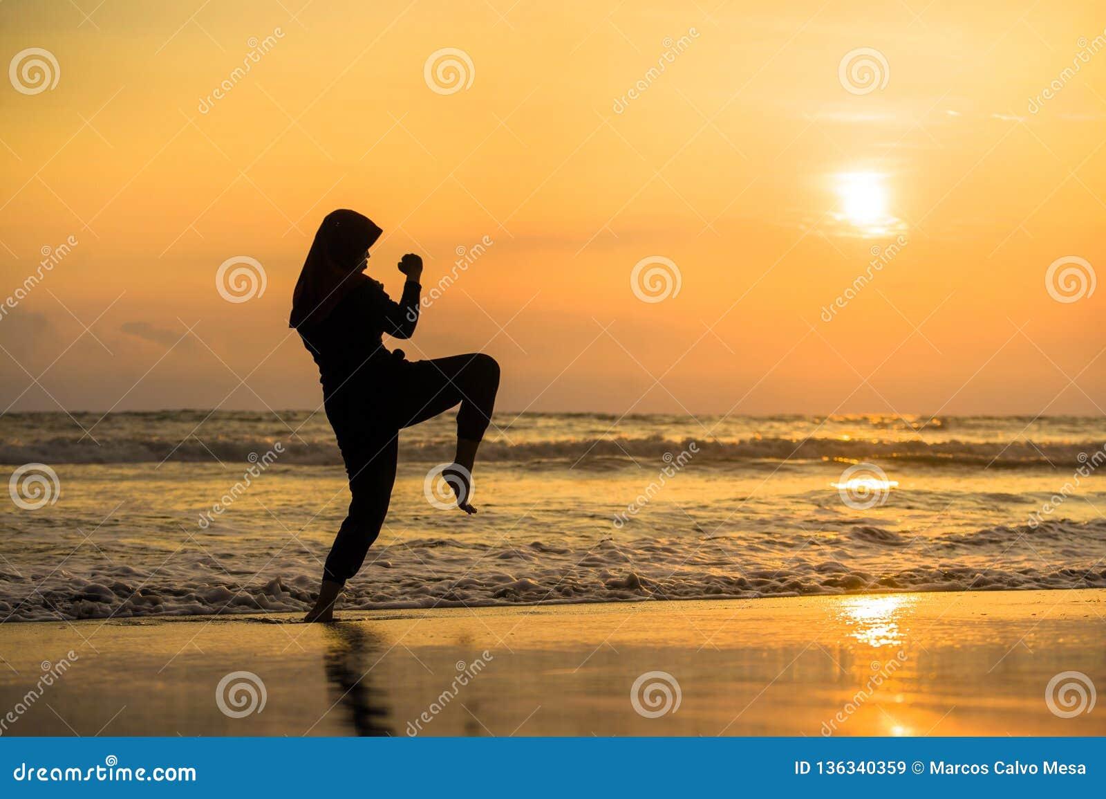 Silhouet van jonge geschikte Moslimvrouw omvat in Islam hijab de de hoofdsjaal van de de karateschop van opleidingsvechtsporten a