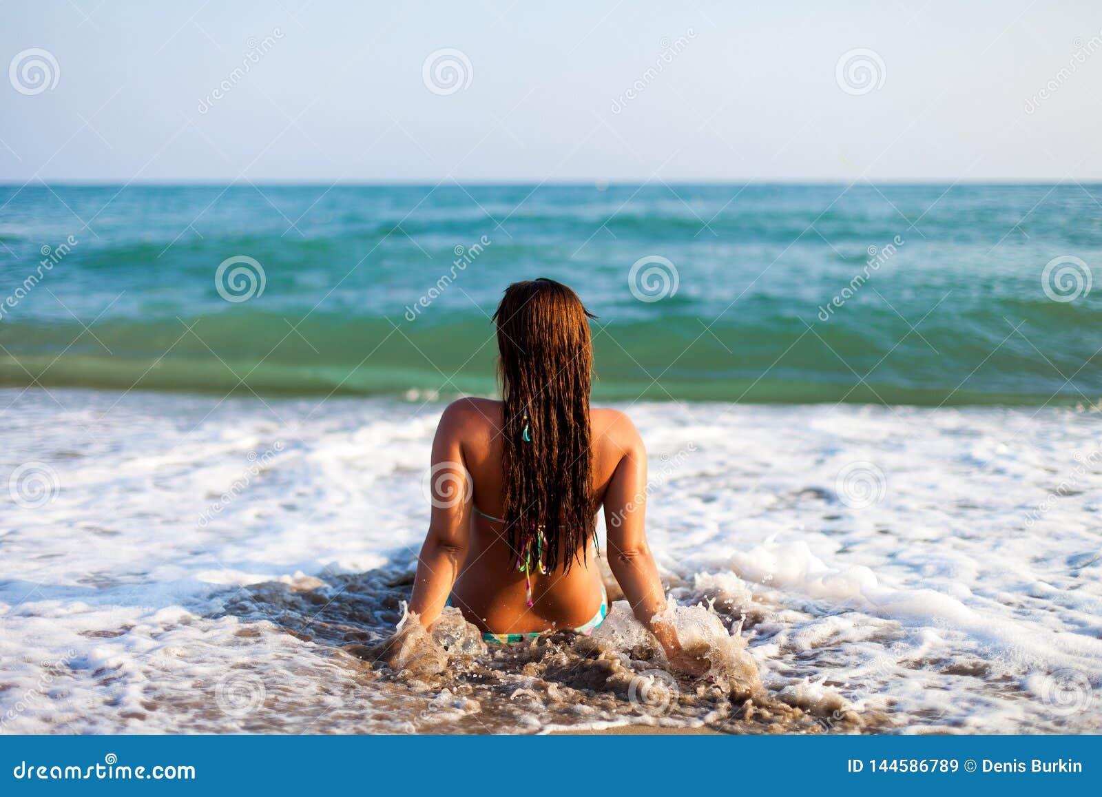 Silhouet van jonge vrouw op strand Jonge vrouwenzitting voor de kust Meisje in bikini het ontspannen op het strand Vrouw
