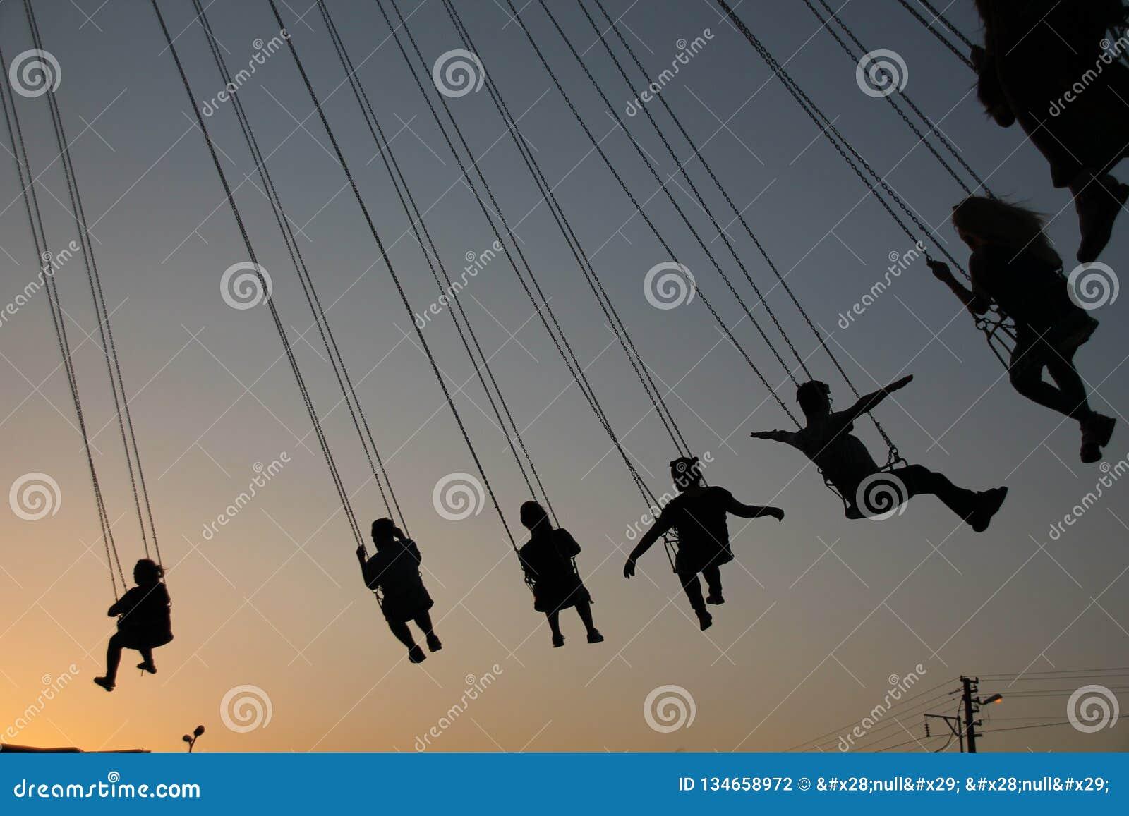 Silhouet van jongeren op Reuzenrad en slingerende carrousel in eindemotie op zonsondergangachtergrond