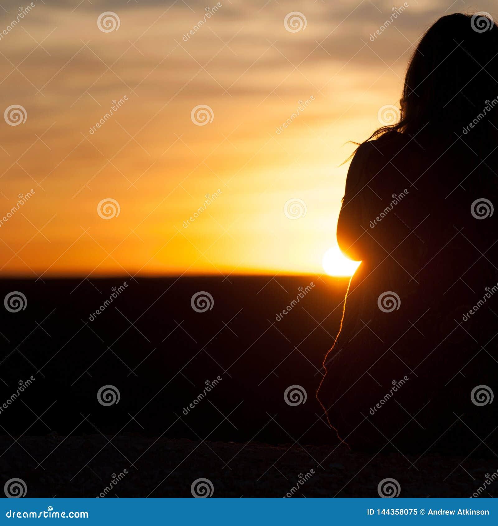 Silhouet van meisje die de oranje en gele zonsopgang/de zonsondergang bekijken