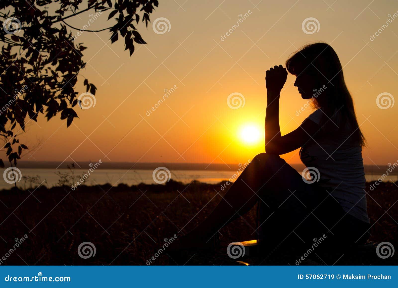 Silhouet van meisje het bidden