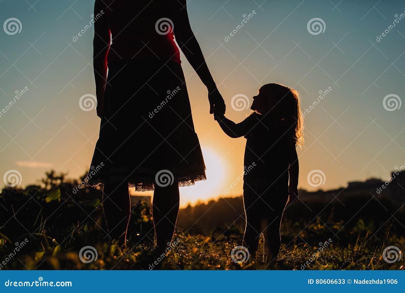 Silhouet van moeder en dochterholdingshanden bij zonsondergang