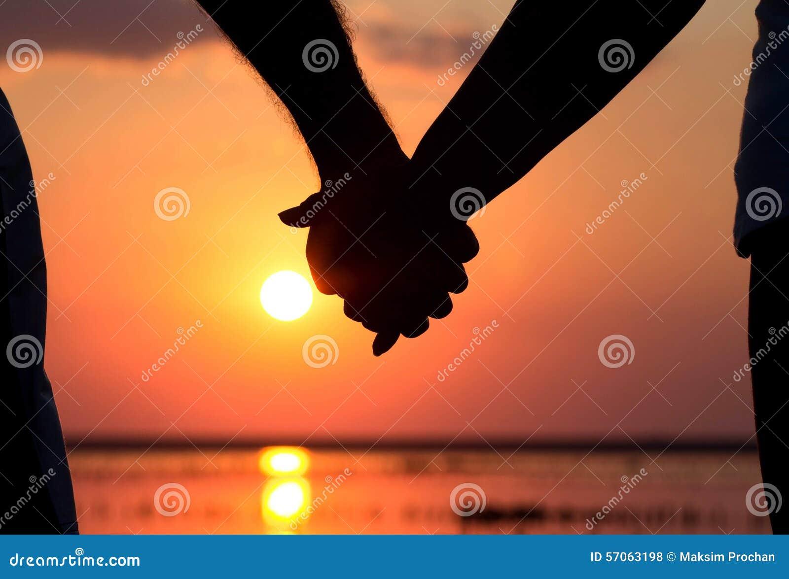Silhouet van paar bij de handen van de zonsondergangholding