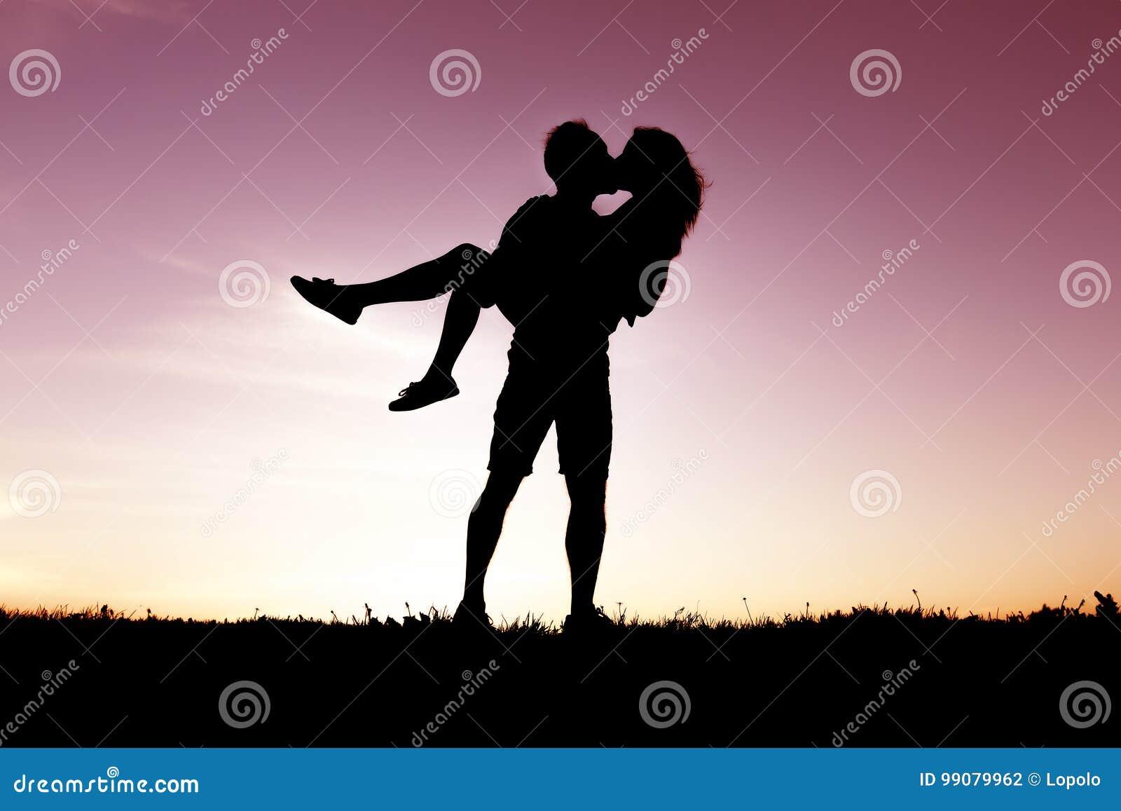 Silhouet van romantische minnaars met zonsondergang op de rug