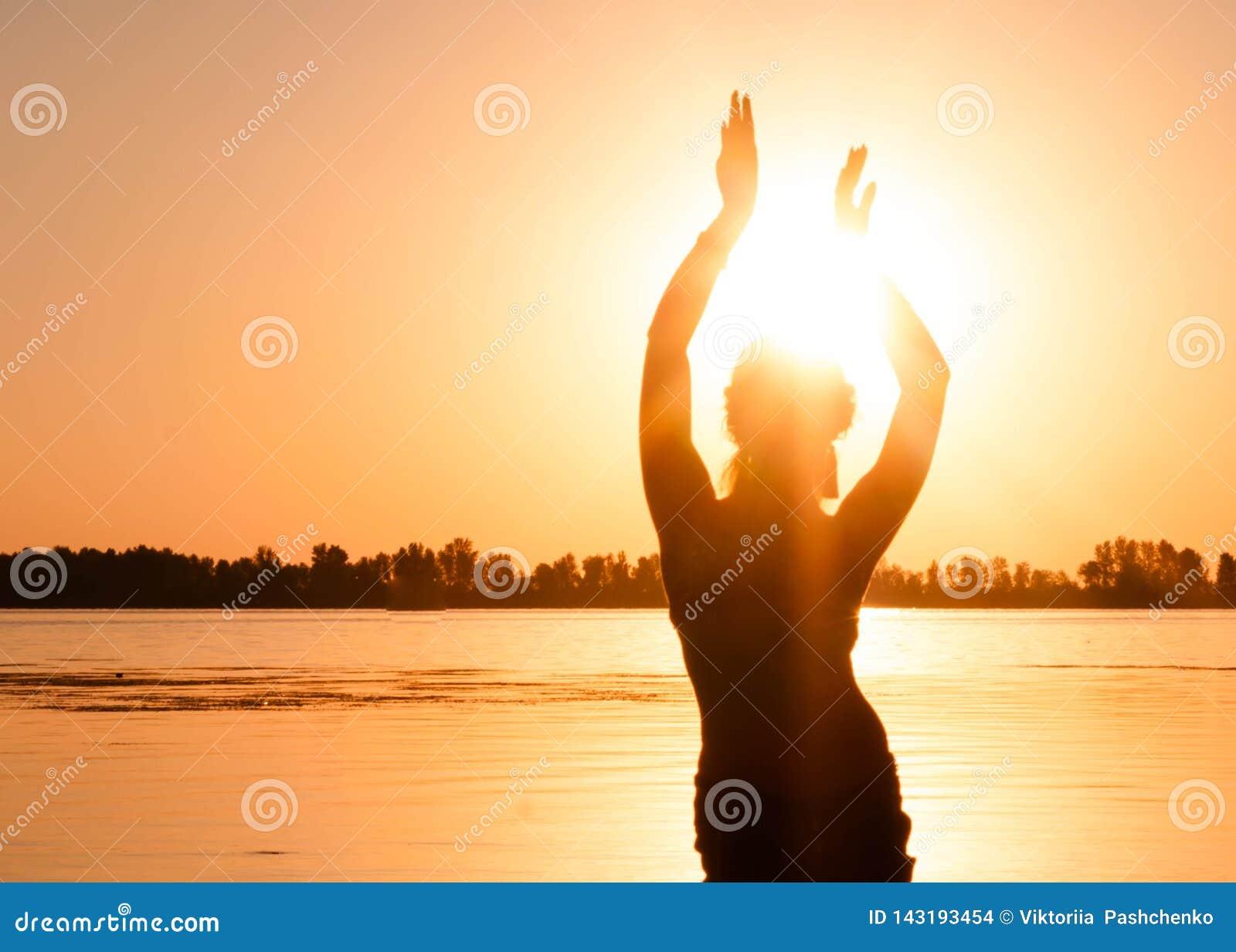 Silhouet van slanke vrouw het dansen traditionele stammenbuikdans op strand bij zonsopgang