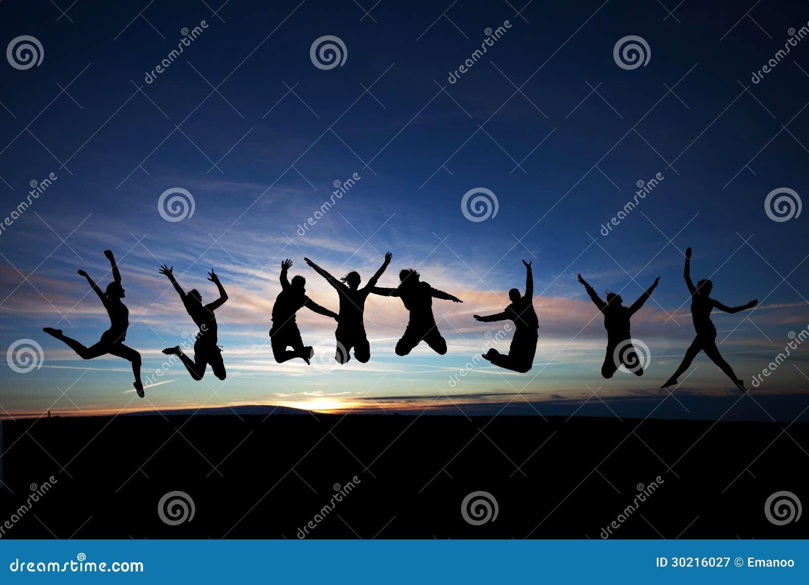 Tieners die in zonsondergang springen