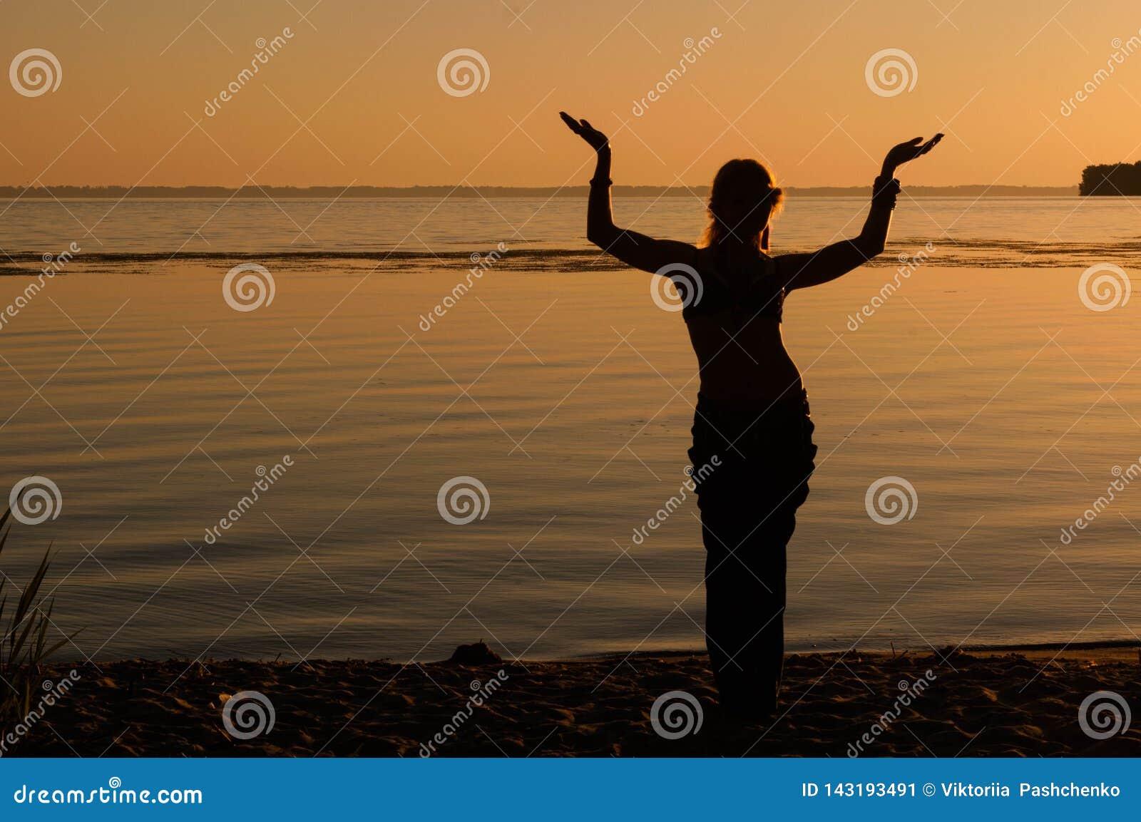 Silhouet van vrouw het dansen traditie trible oosterling dichtbij grote rivierkust