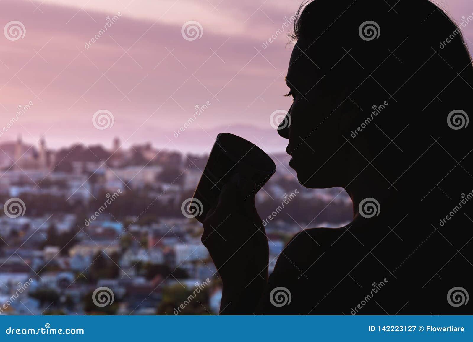 Silhouet van vrouw met kop thee op de de stadsachtergrond van Chicago