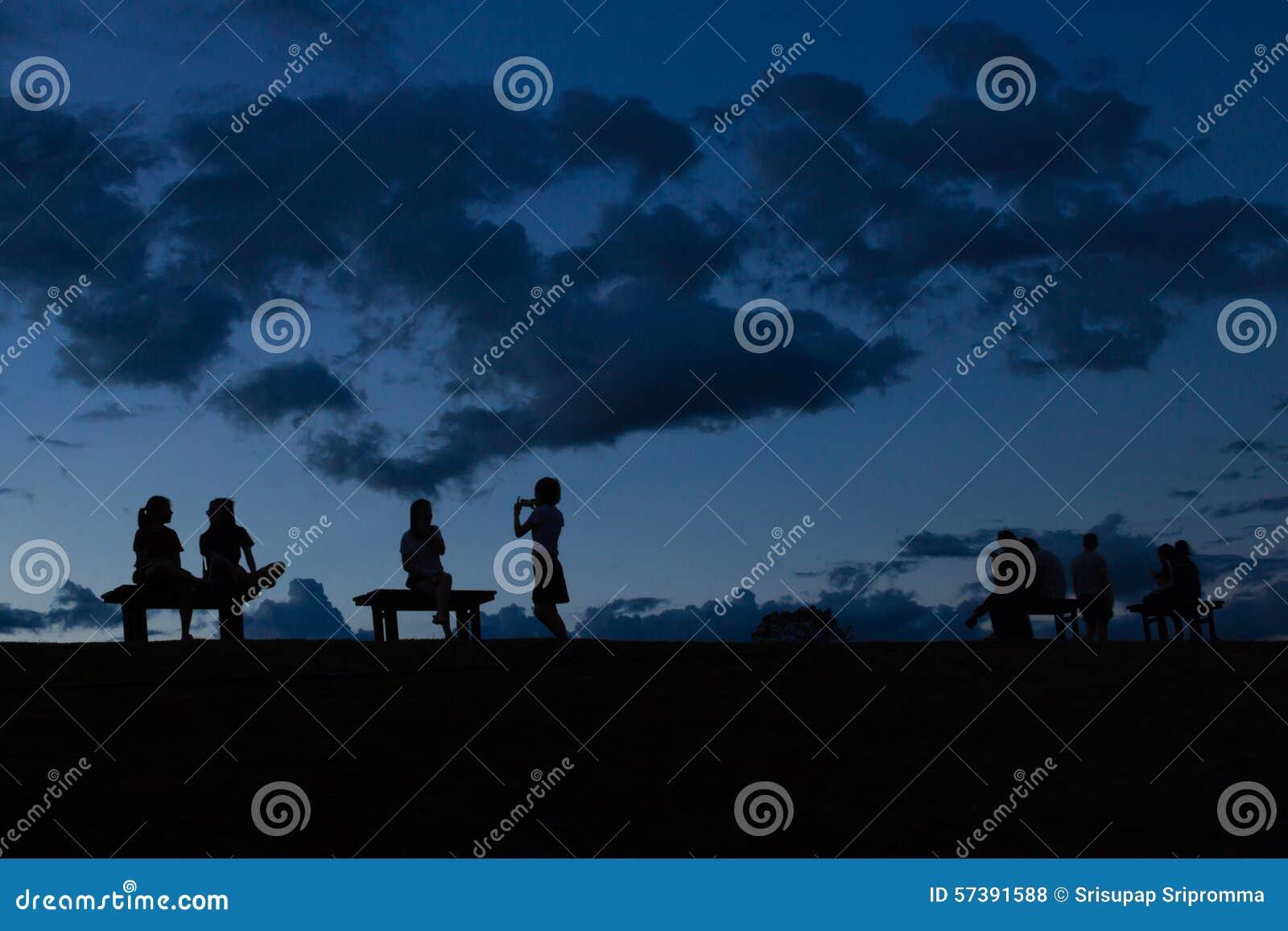 Silhouetmensen die op de tak zitten