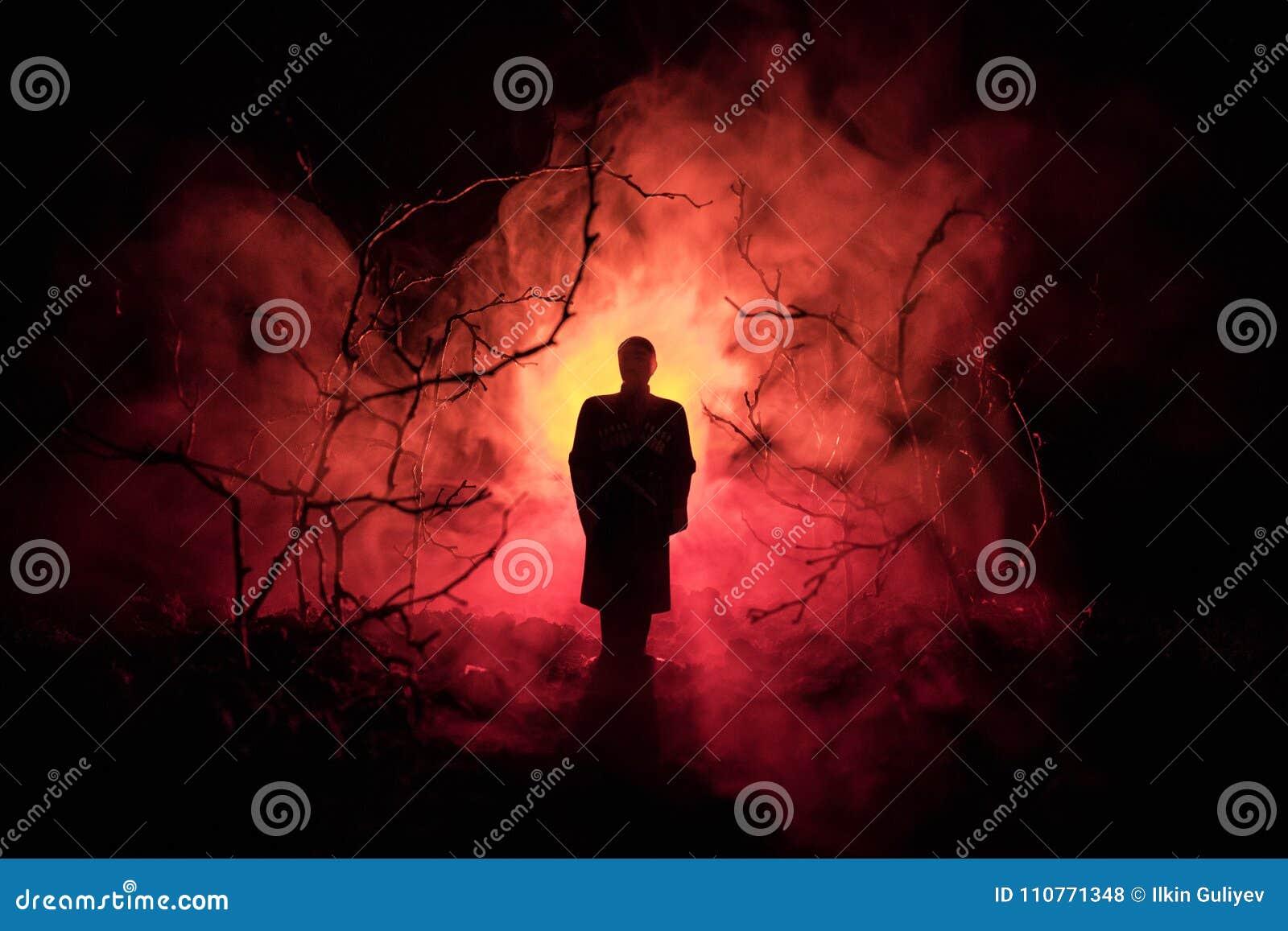 Silhouette étrange dans une forêt fantasmagorique foncée la nuit, lumières surréalistes de paysage mystique avec l homme rampant